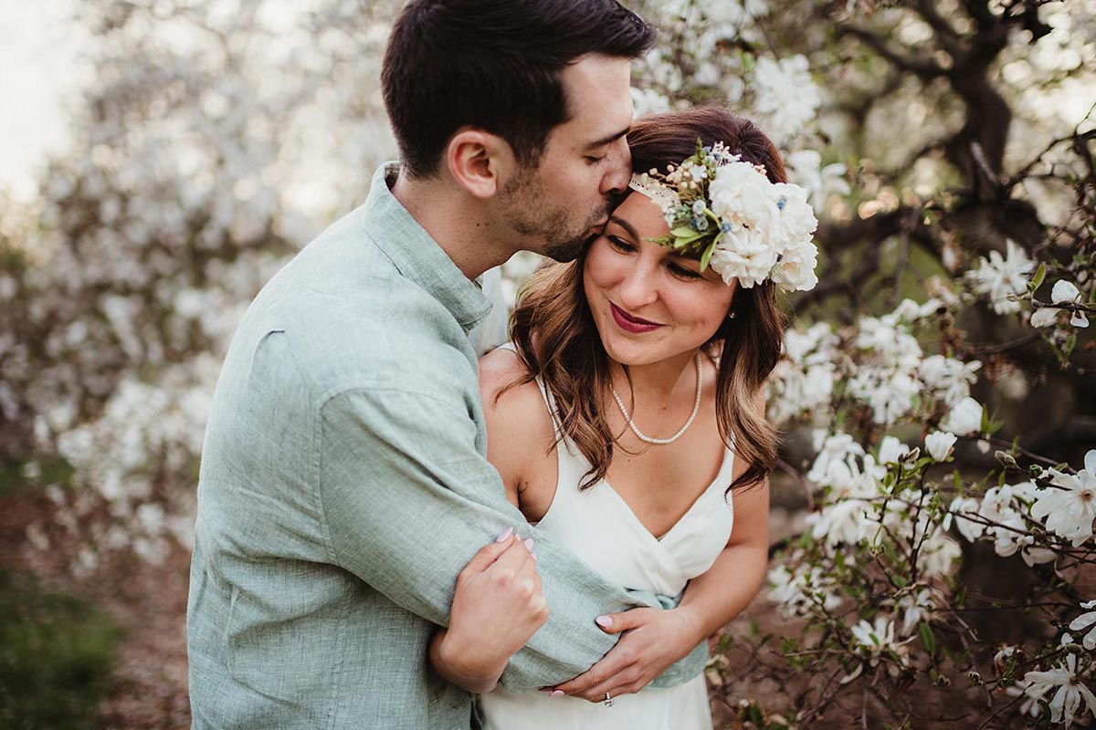 Engagement Couple Snuggling Spring Blooms