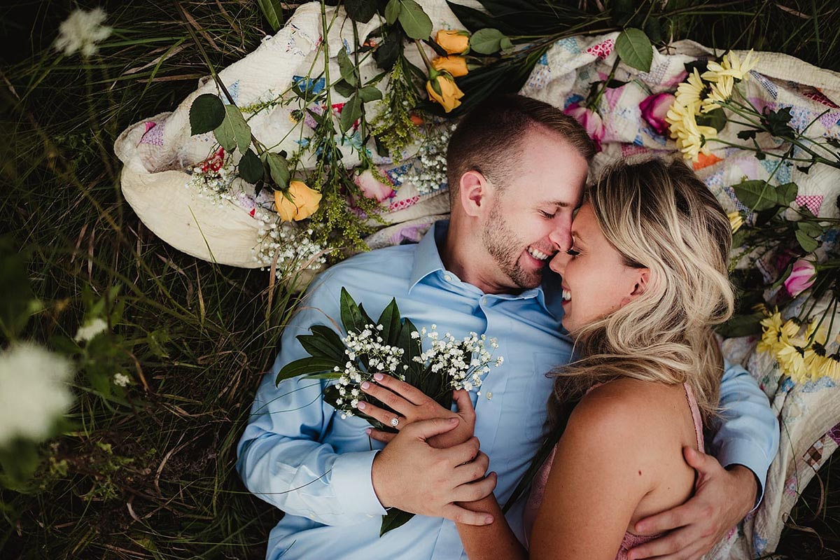Engagement Couple on Blanket with Flowers