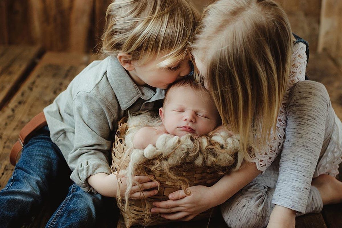 Siblings Kissing Newborn Brother