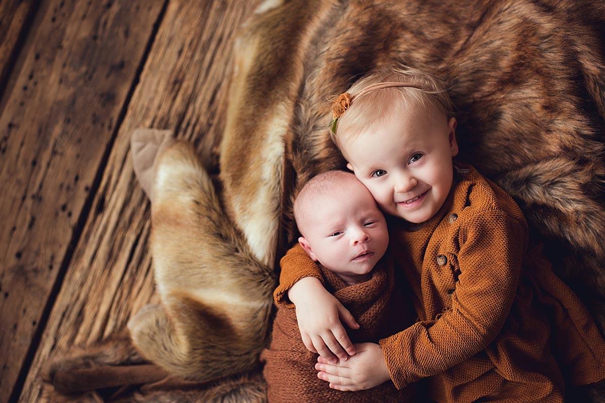 Newborn Snuggled by Sister