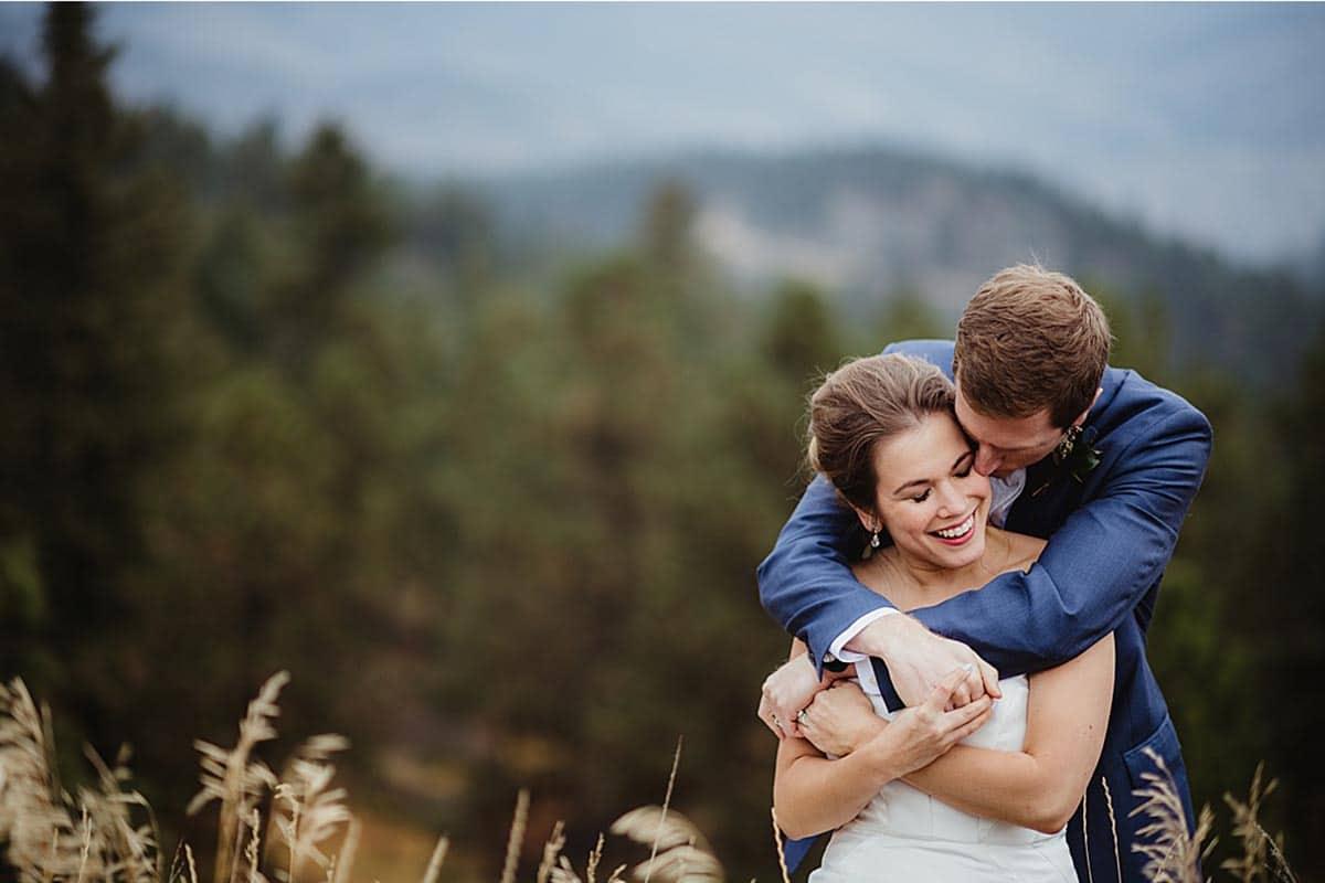 Groom Hugging Bride Mountain Background