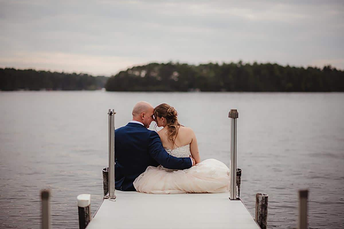 Bride and Groom Sitting on Pier