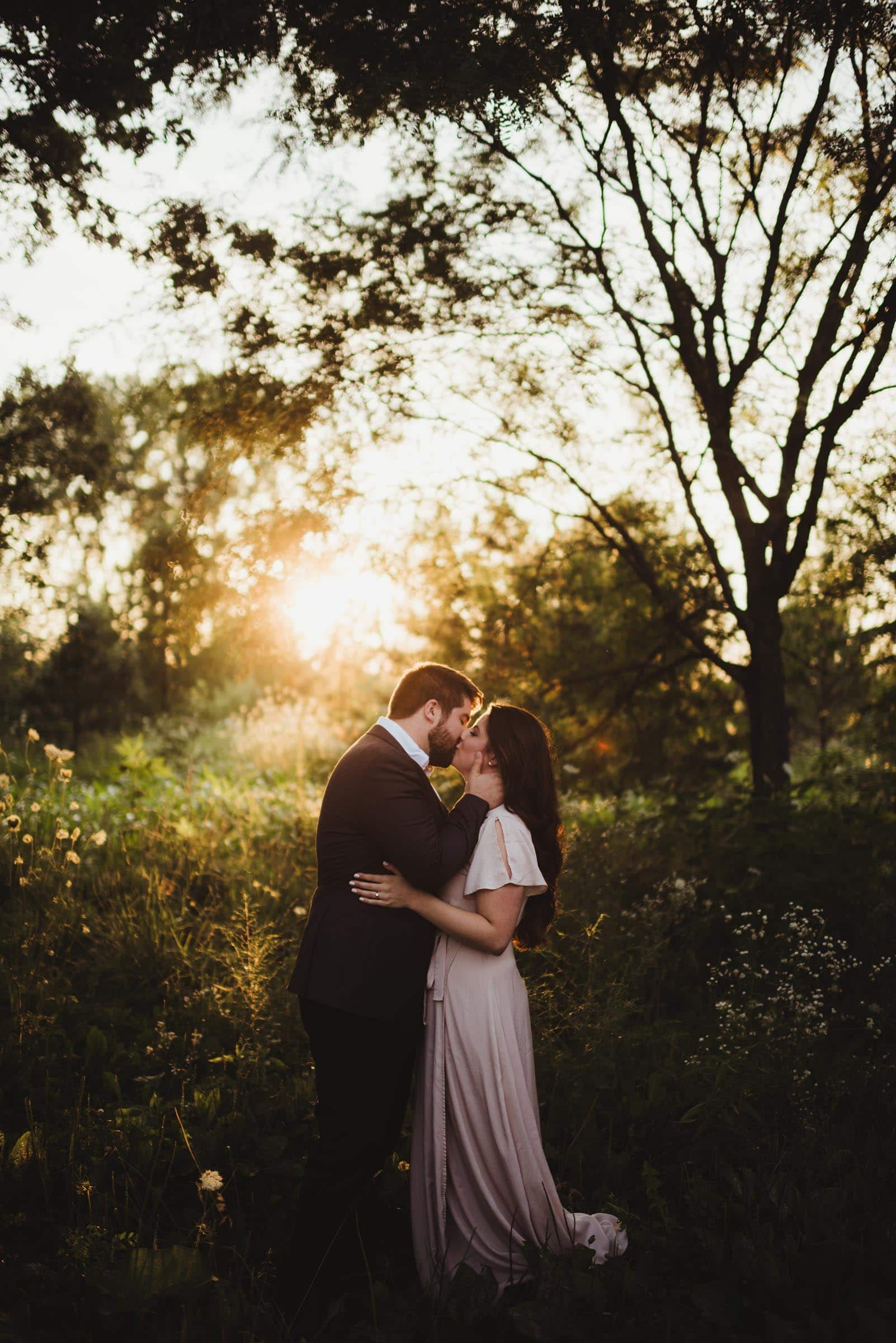 couple kissing in a field of golden light