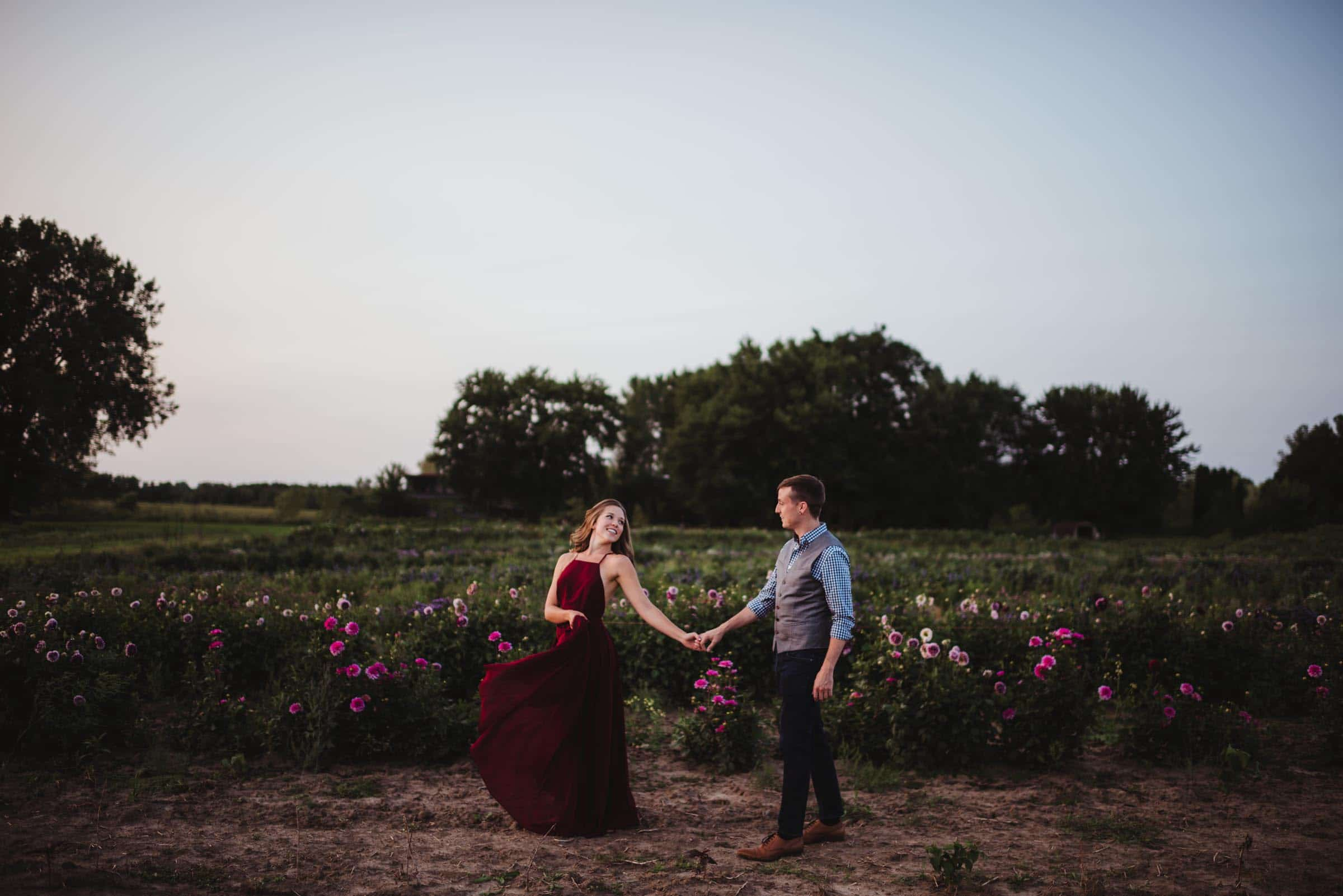 couple walking together in a field of flowers