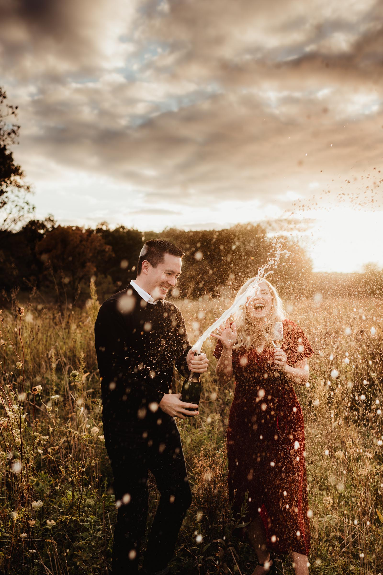 couple popping champagne in a field at sunset