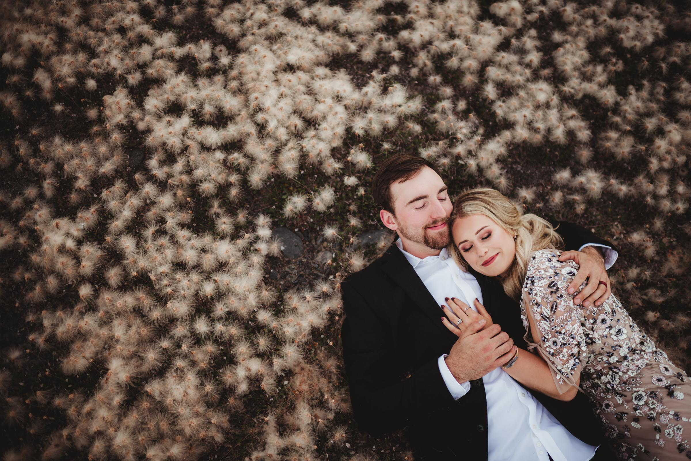 couple laying in a field of cotton flowers
