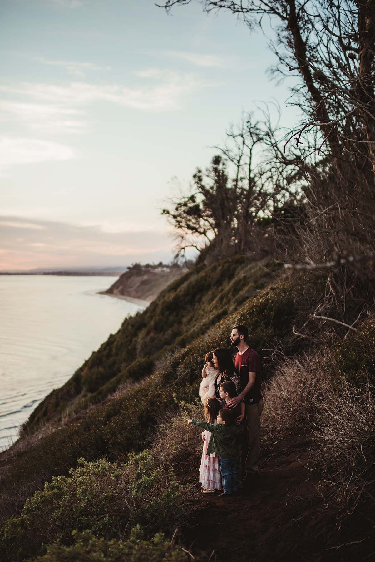 family by the ocean near a cliff lookout