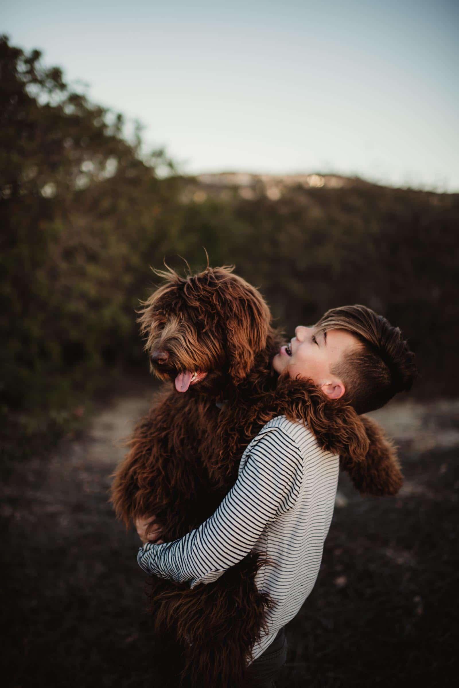 boy hugging a golden doodle
