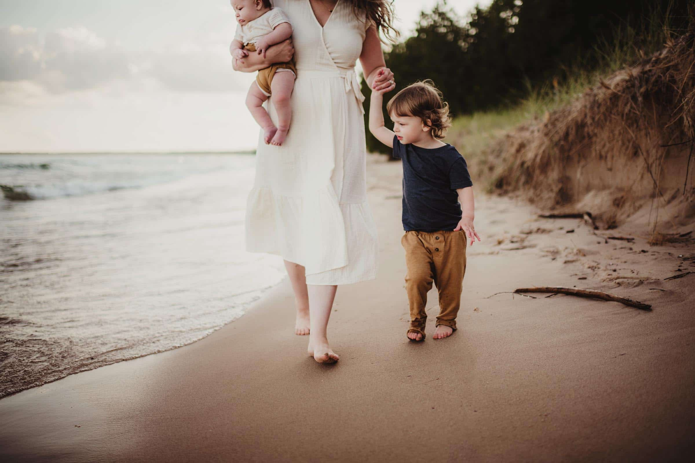 mom and sons walking on a beach