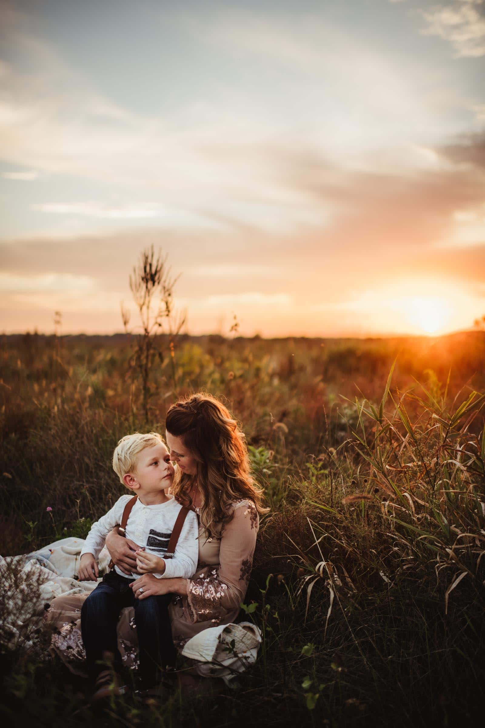 son listening to mother while on her lap in a field