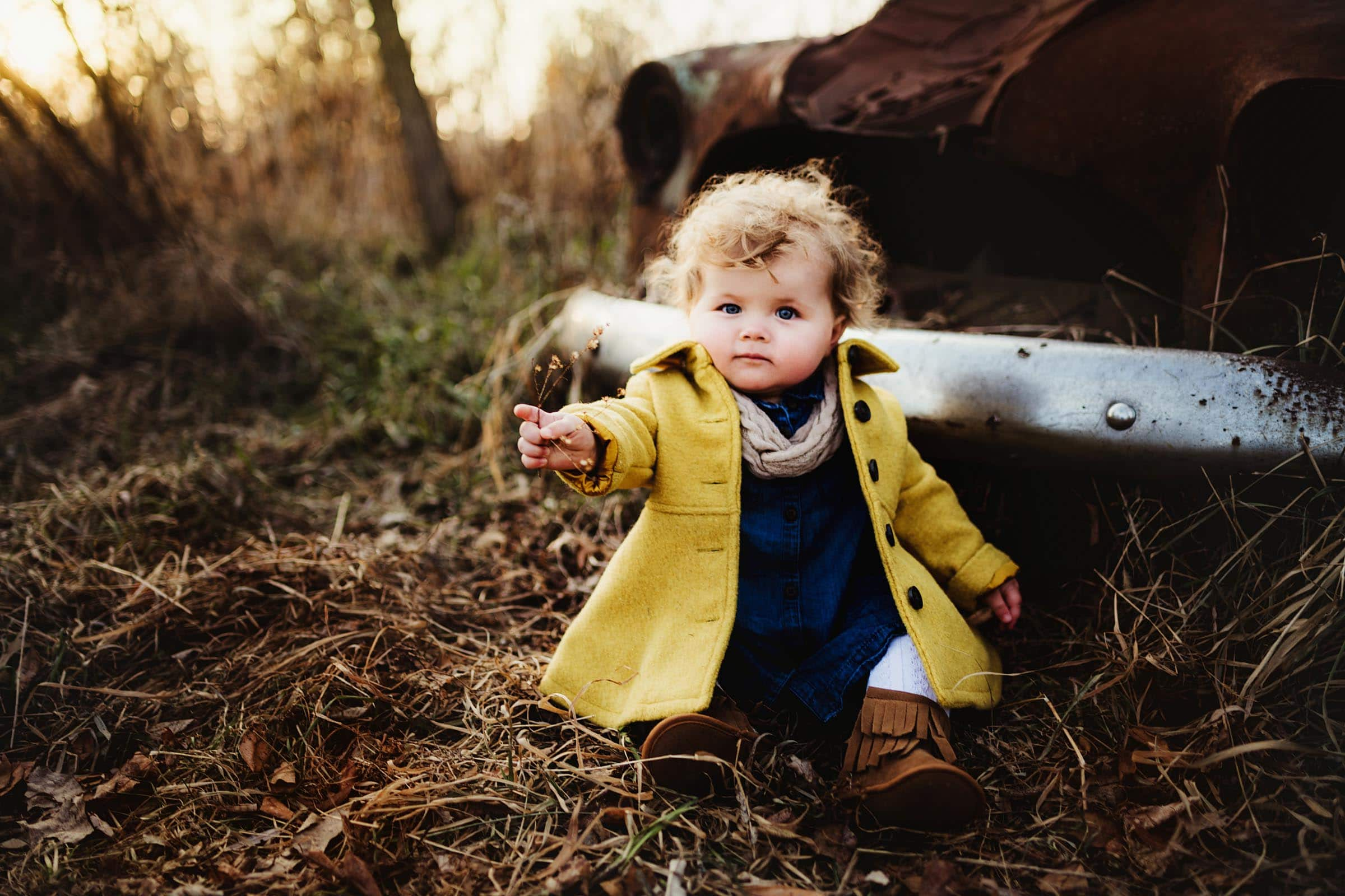 toddler in a yellow jacket sitting by old car