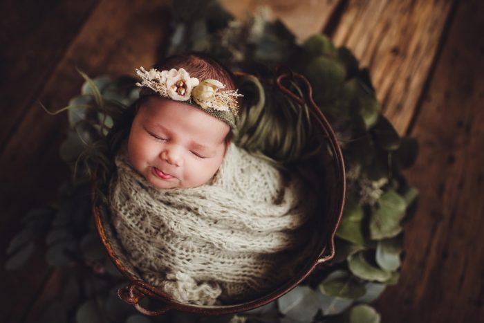 baby swaddled in bucket with floral tie back