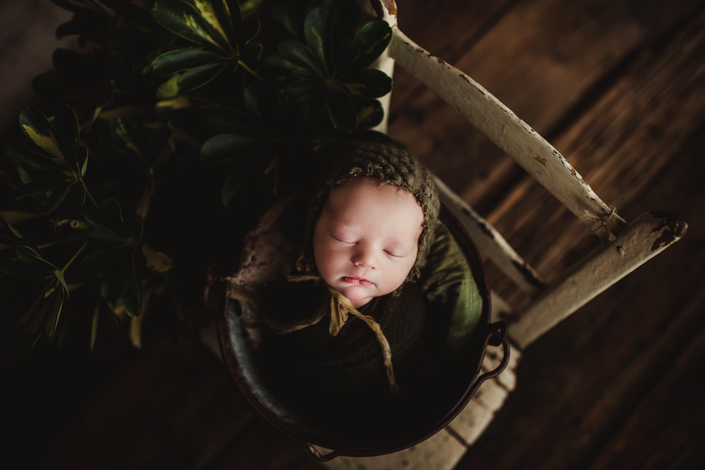 newborn baby wrapped and on a chair and bucket in studio