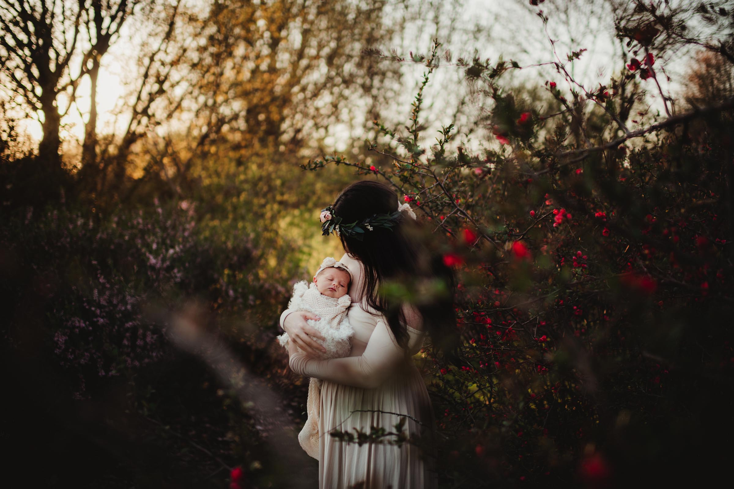 new mother holding her wrapped baby outdoors by red flowers