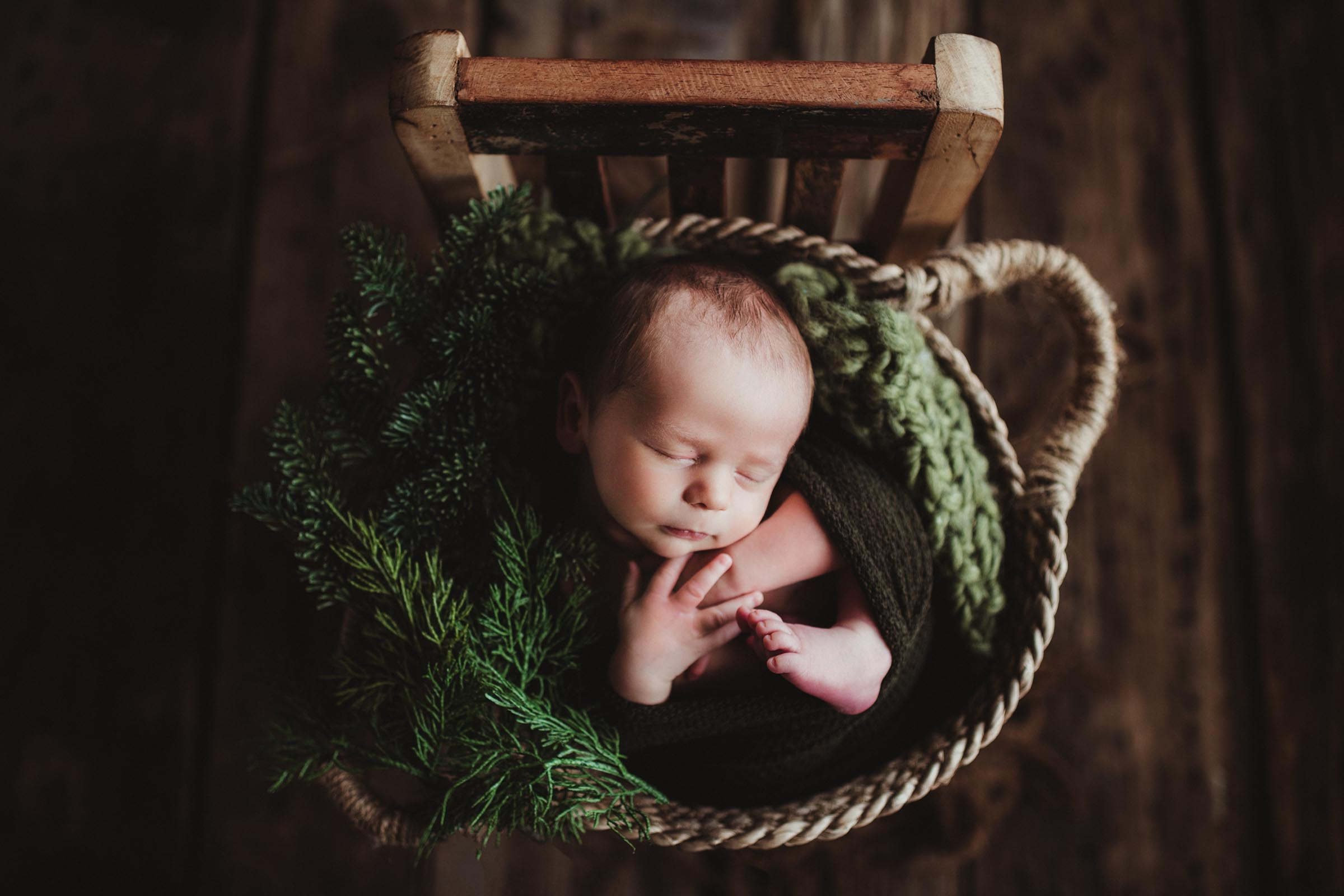 baby loosely wrapped in green blanket in a basket in studio