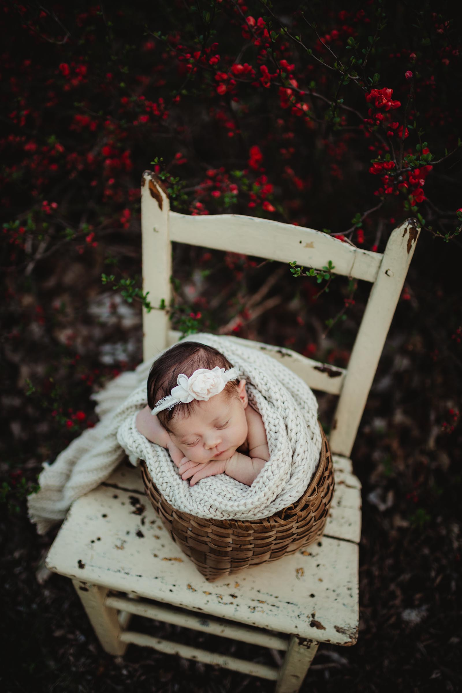 baby sleeping in bucket pose with floral headband