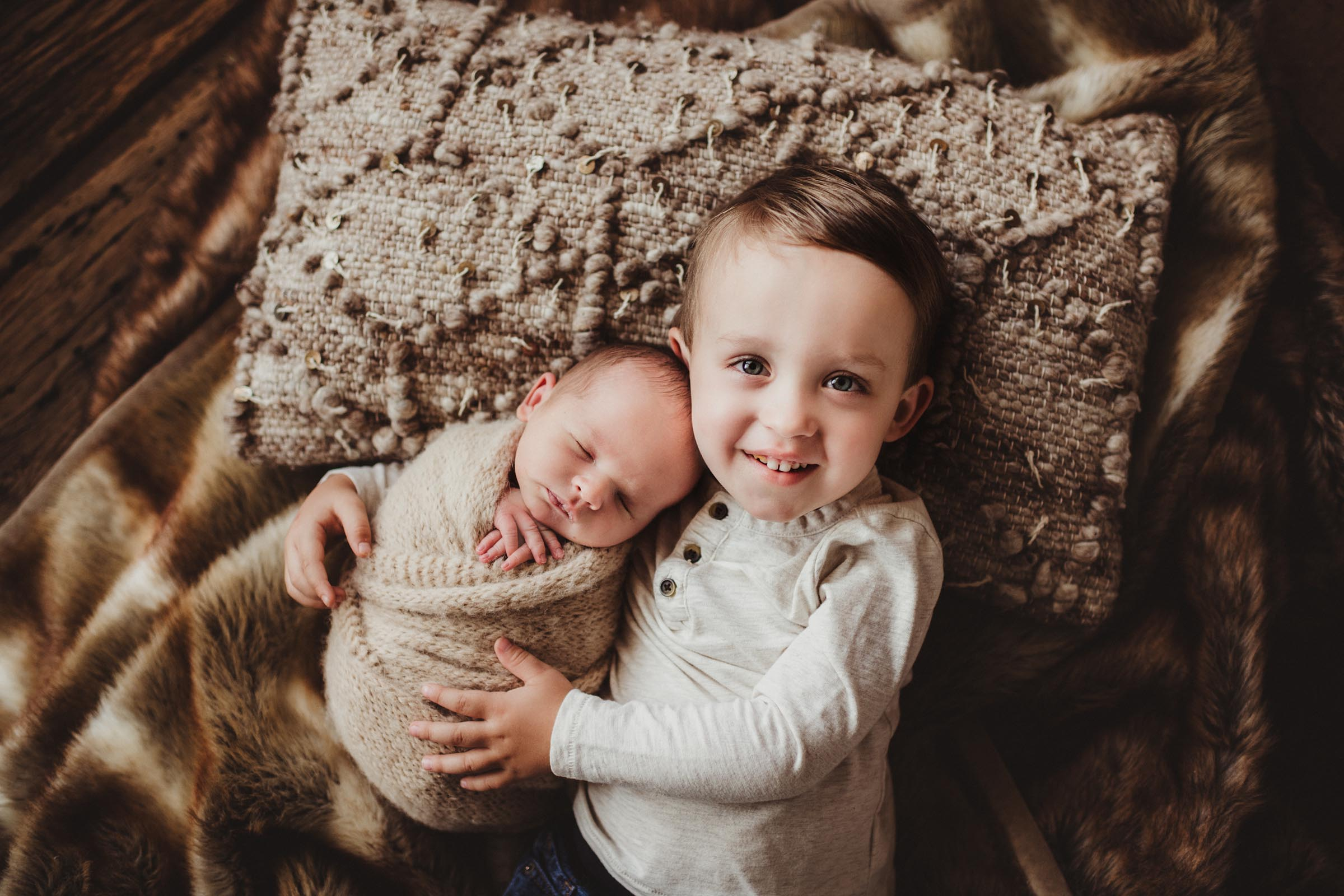 brother hugging his wrapped baby brother