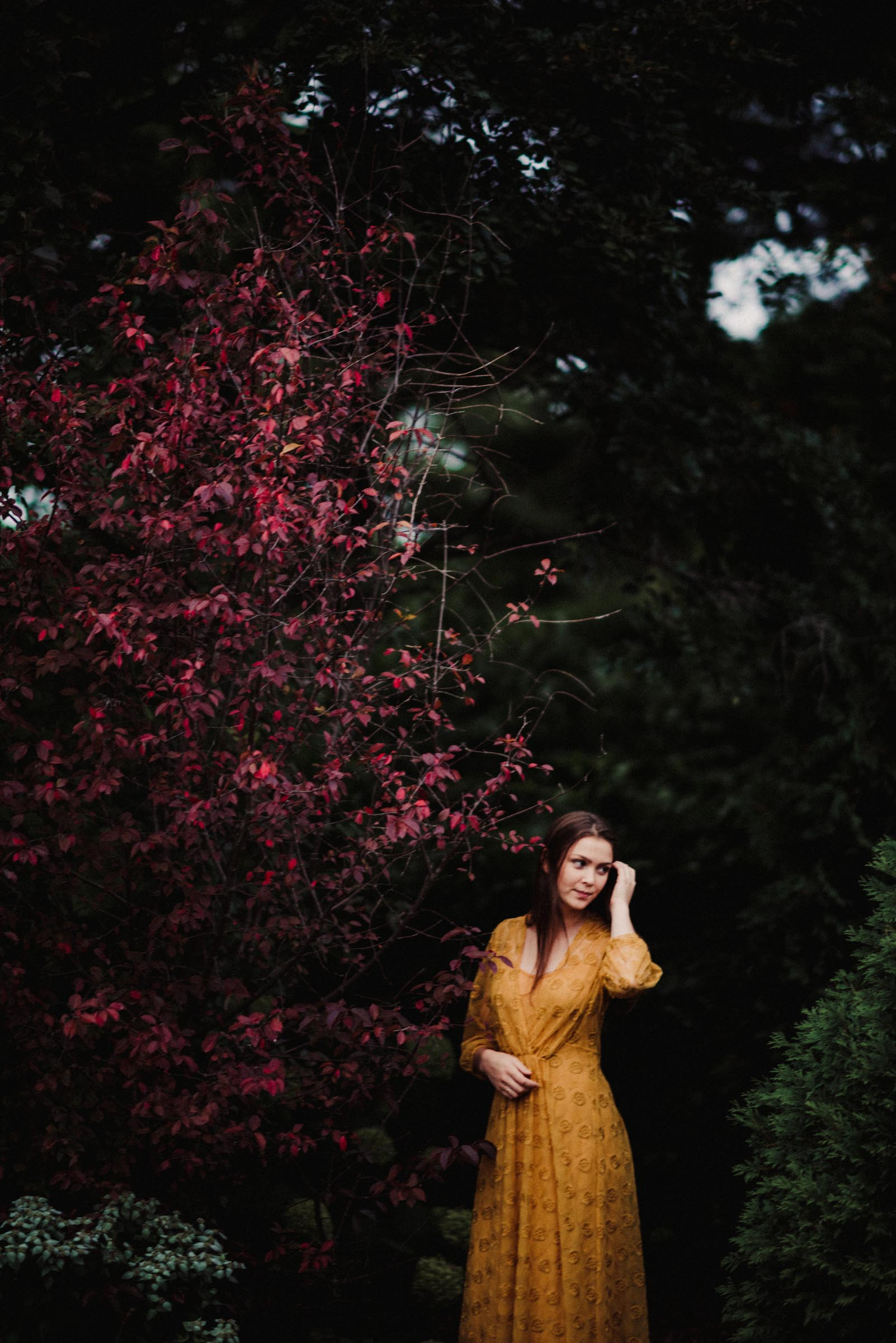senior girl in yellow dress by red flowers
