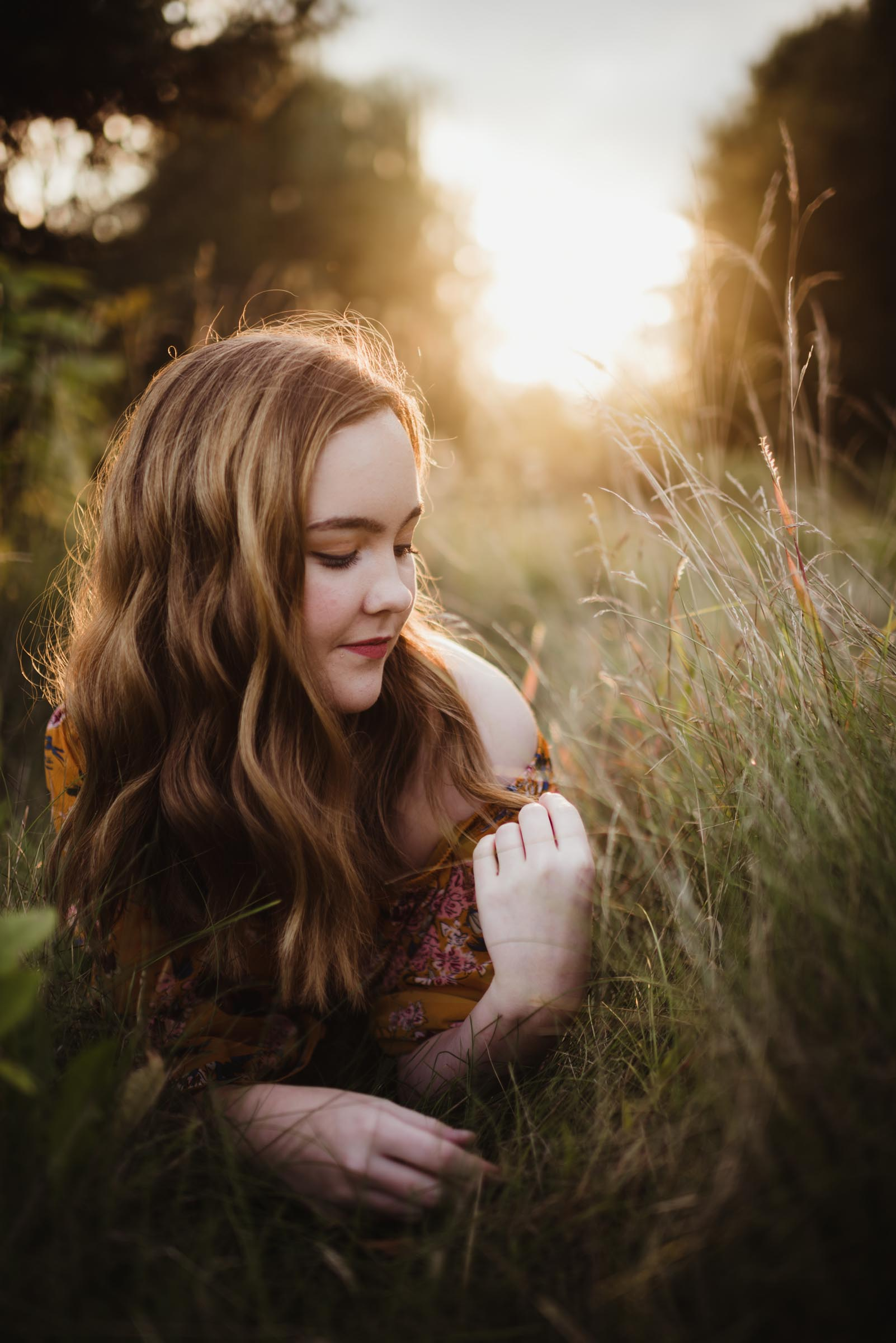 senior girl laying in a field at sunset