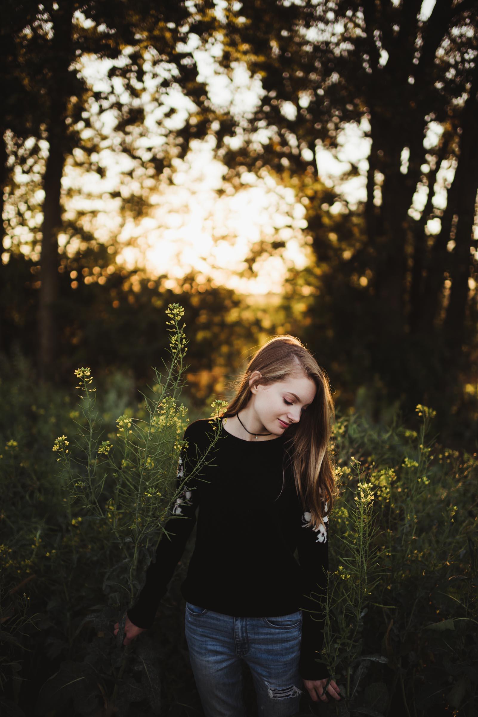 senior girl standing in field at sunset