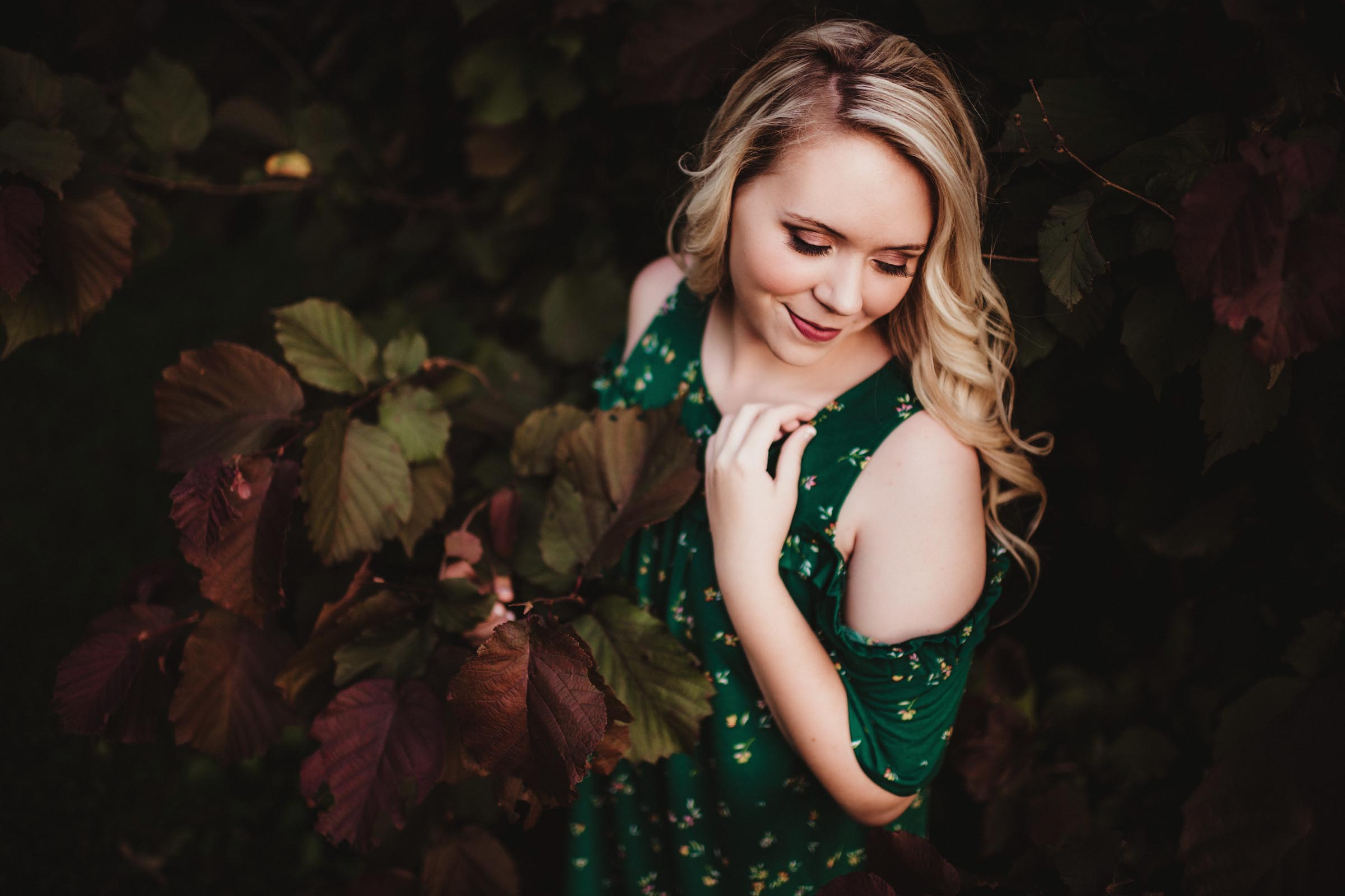 senior girl in green dress by leaves