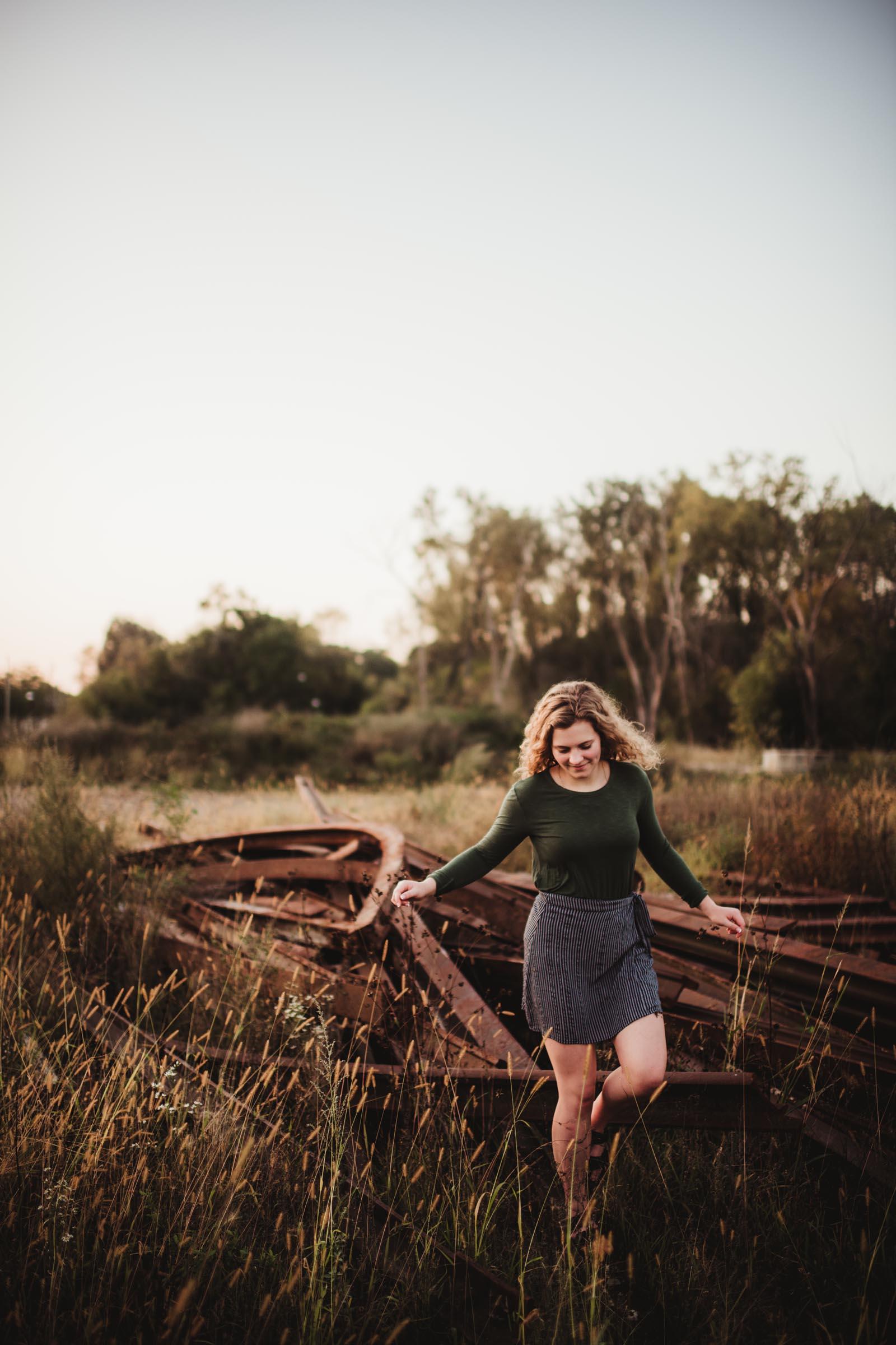 senior girl in a rustic field
