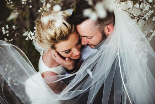 couple wrapped in veil under magnolia flowers