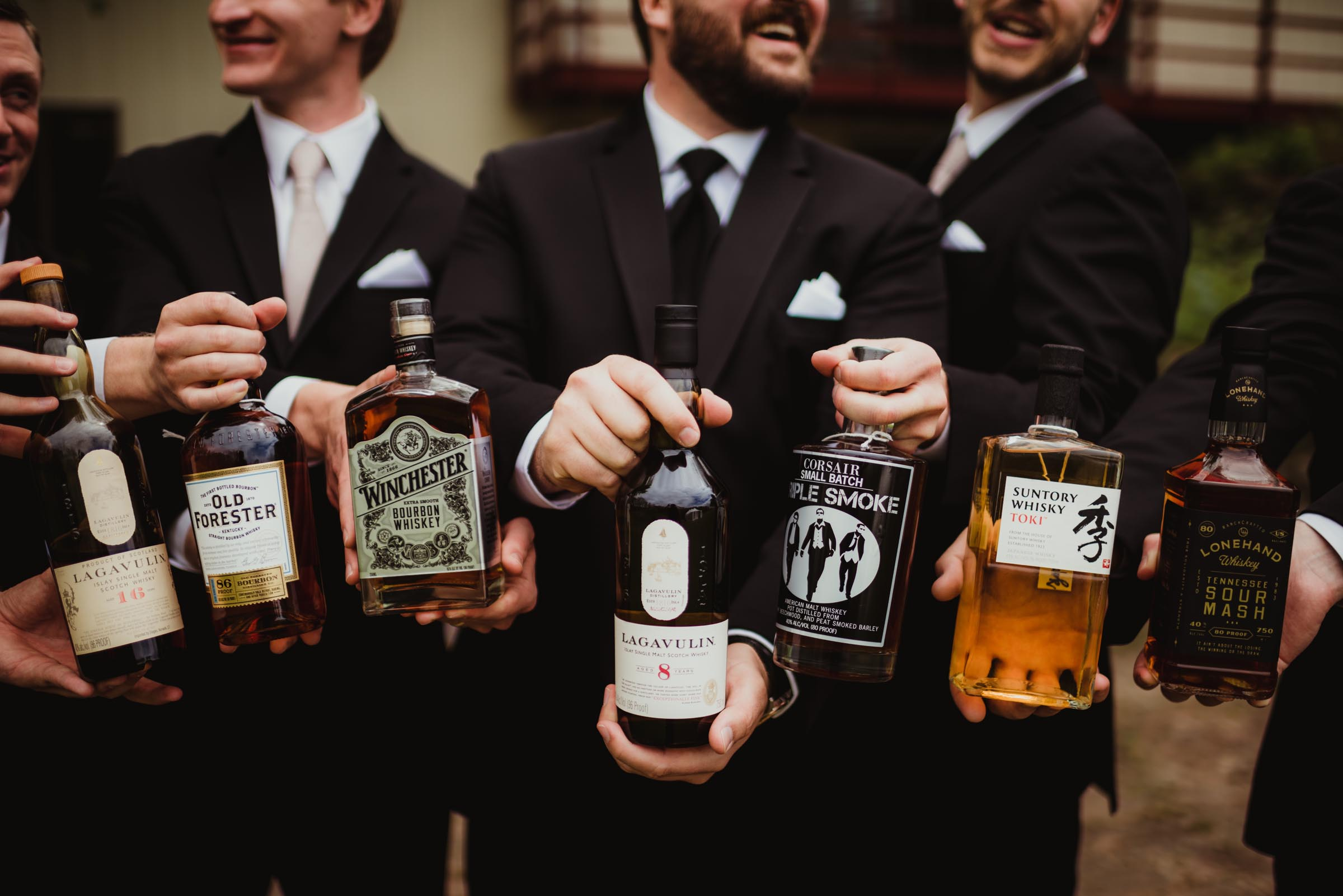 groomsmen holding various whiskey bottles