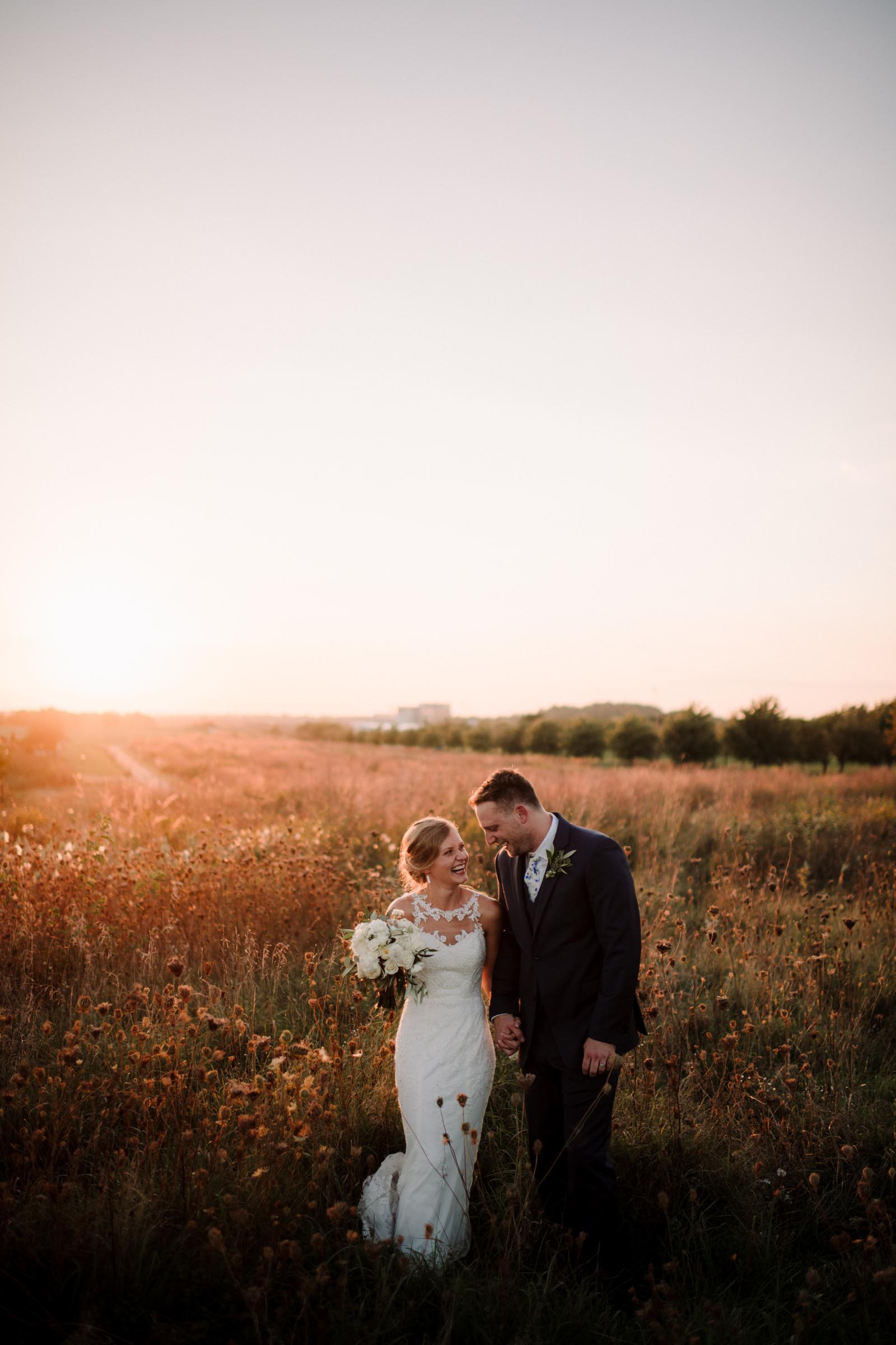 bride and groom in golden field at sunset