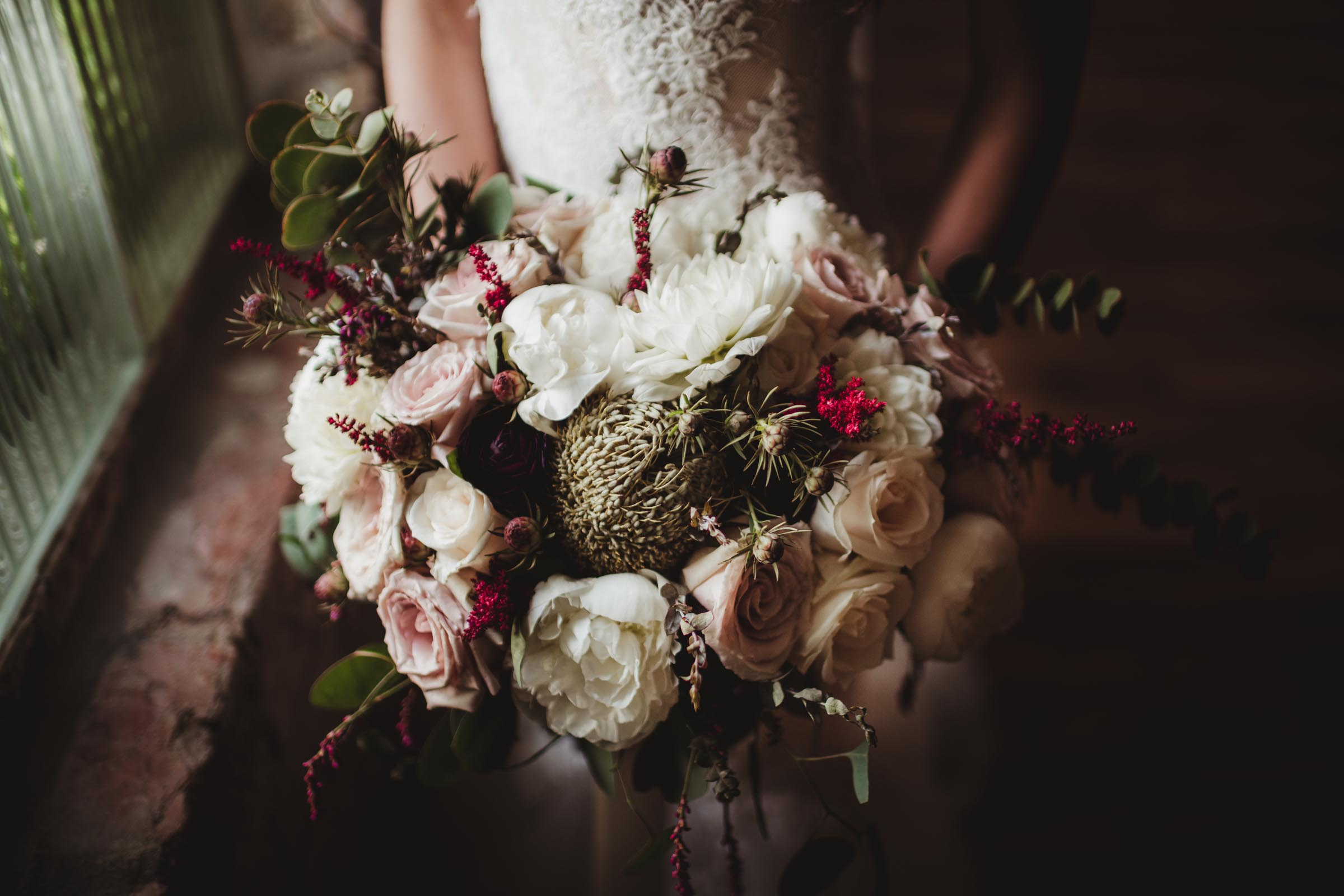 gorgeous bouquet held by bride in old factory