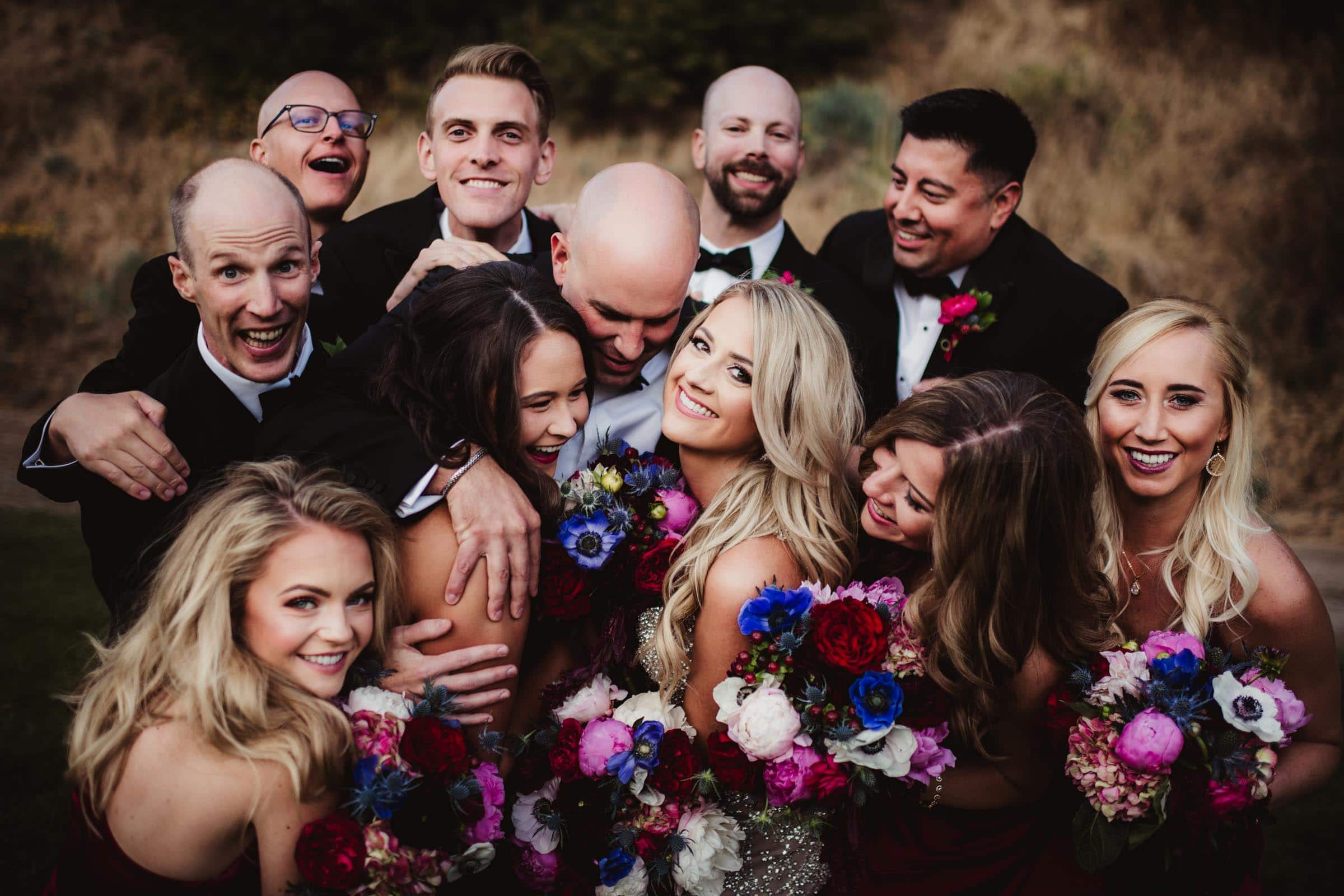 wedding couple surrounded by friends and flowers