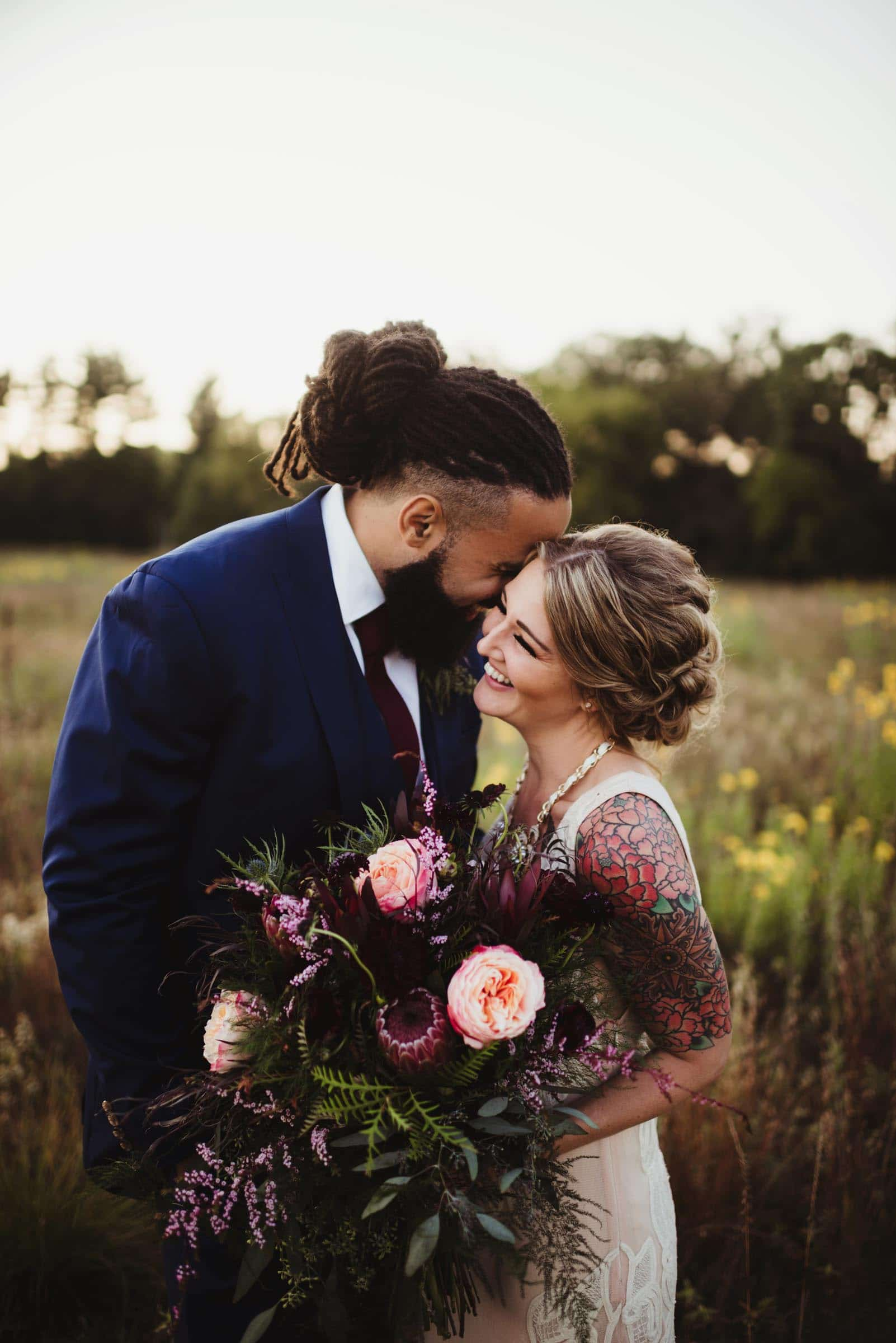 tattoo bride with huge bouquet snuggling with groom in floral field