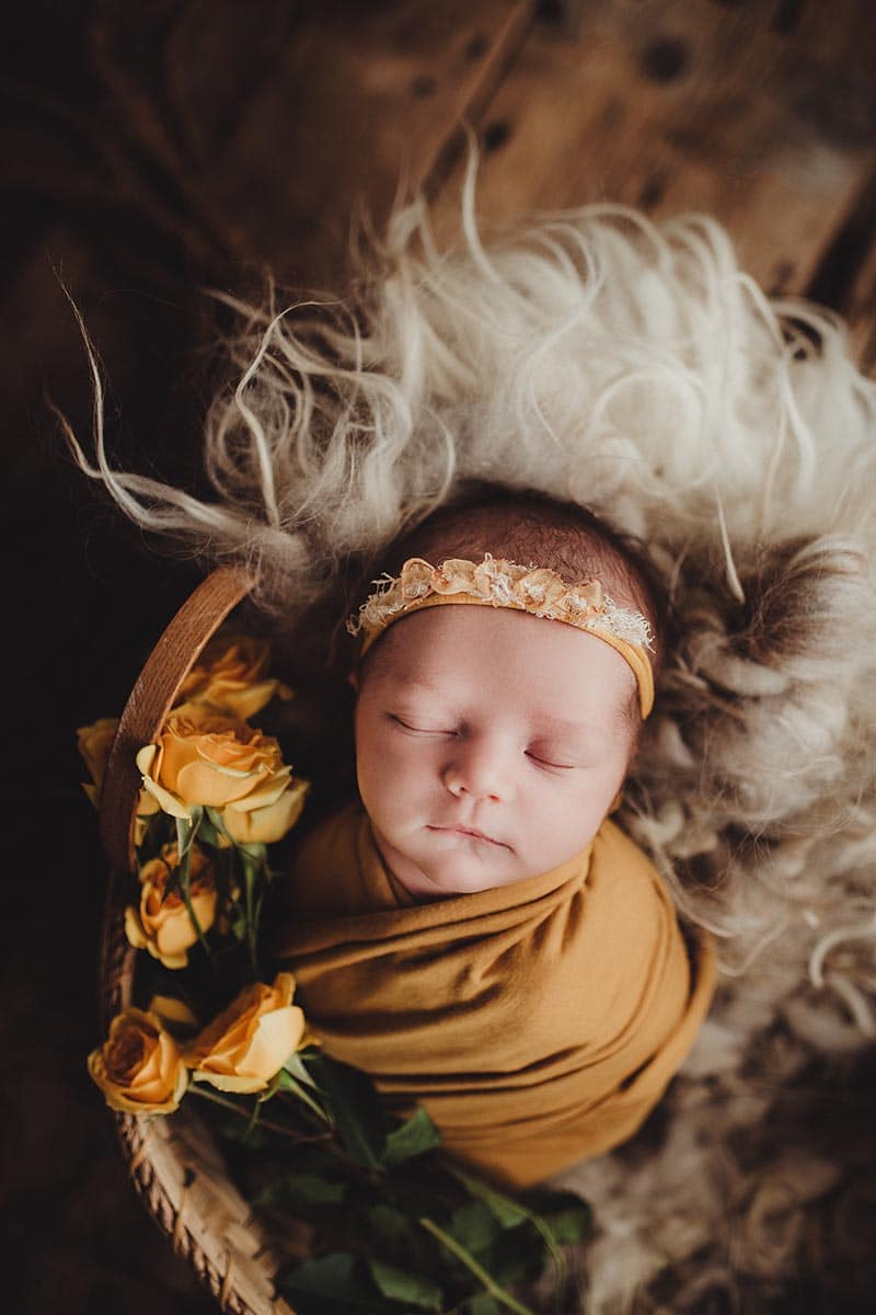 baby swaddled in a yellow wrap in a bowl pose
