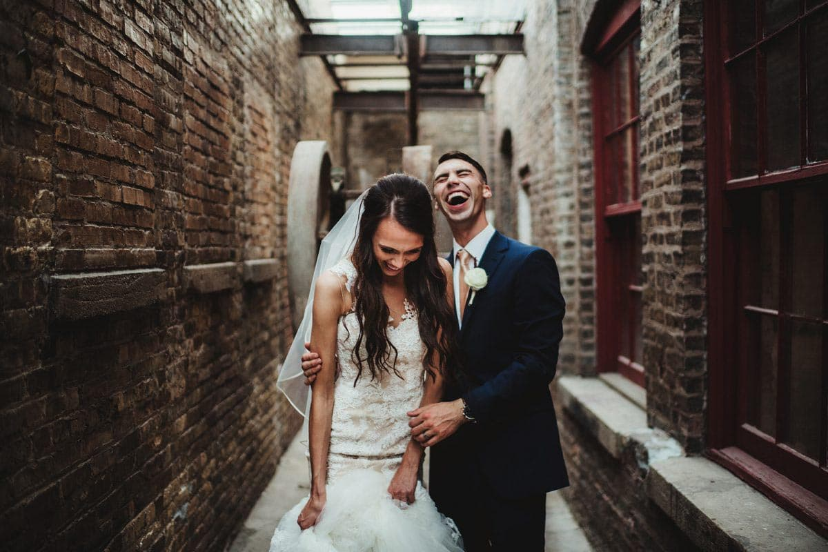 wedding couple laughing together in a brick building