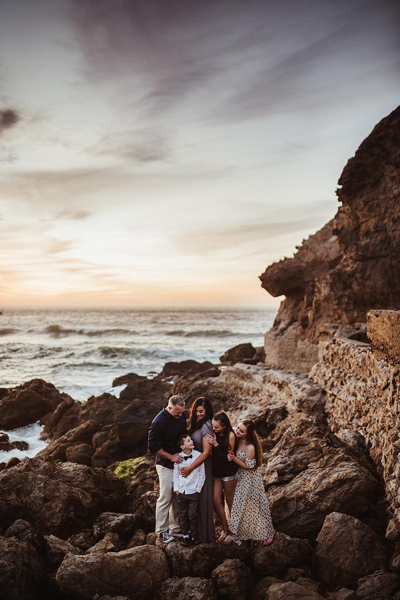 family together on a rocky shore