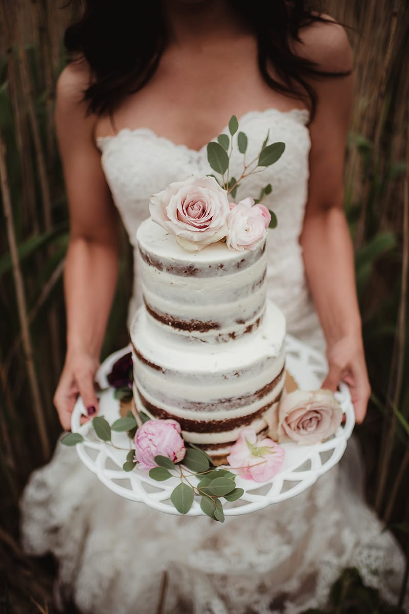 bride holding her wedding cake in a field
