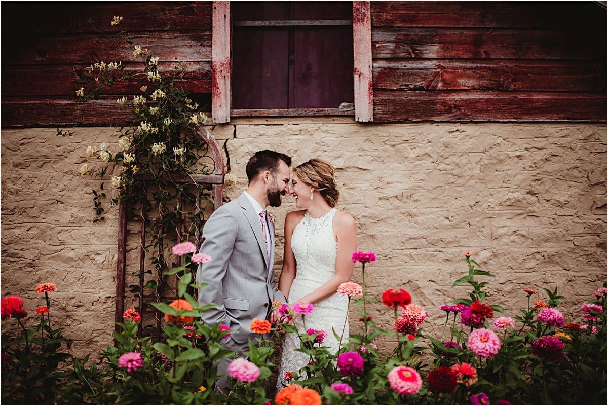 Summer Vineyard Wedding Couple in Flowers by Barn