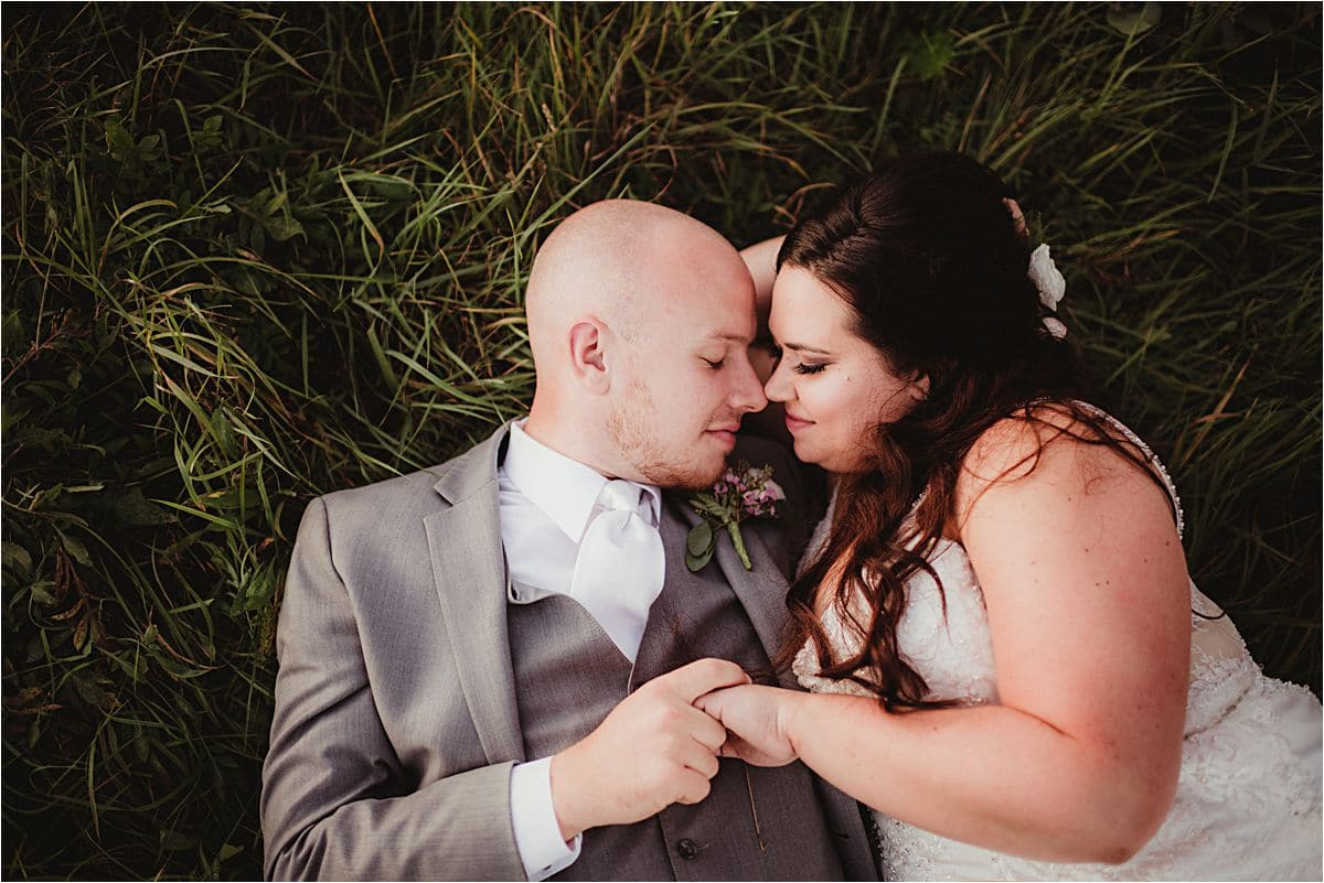 Bride and Groom Laying on Grass