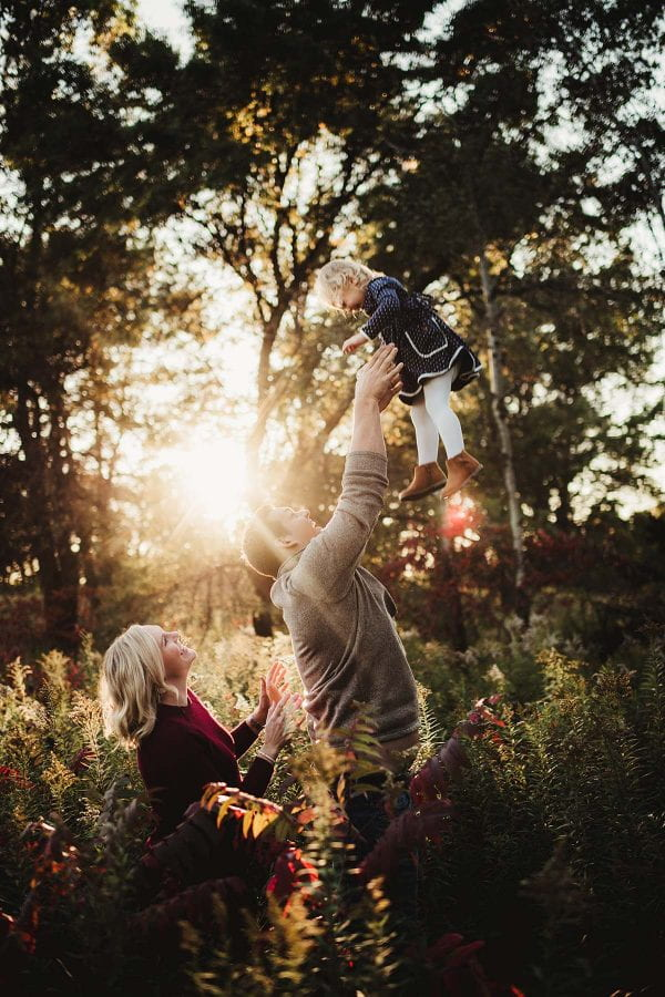 family playing in a forest with sun