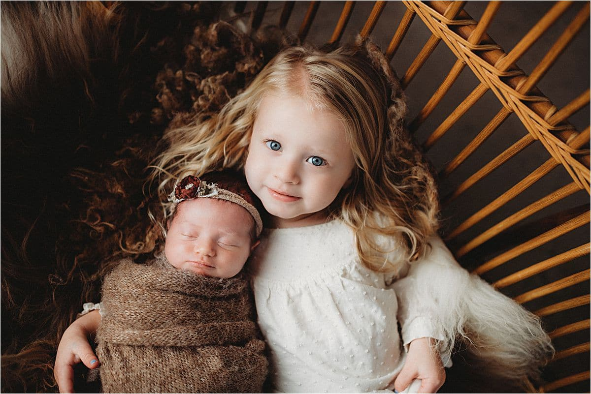 Newborn Girl Snuggled with Sister
