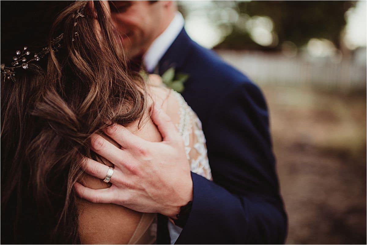 Close Up Groom Hugging Bride