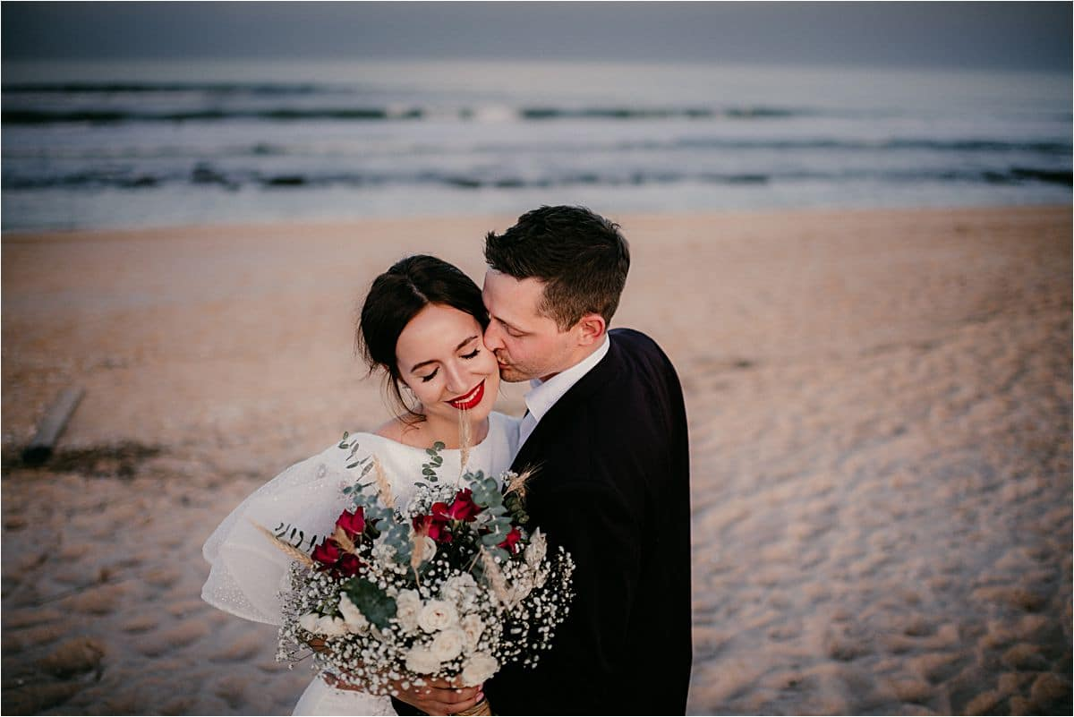 Groom Kissing Bride's Cheek on Beach