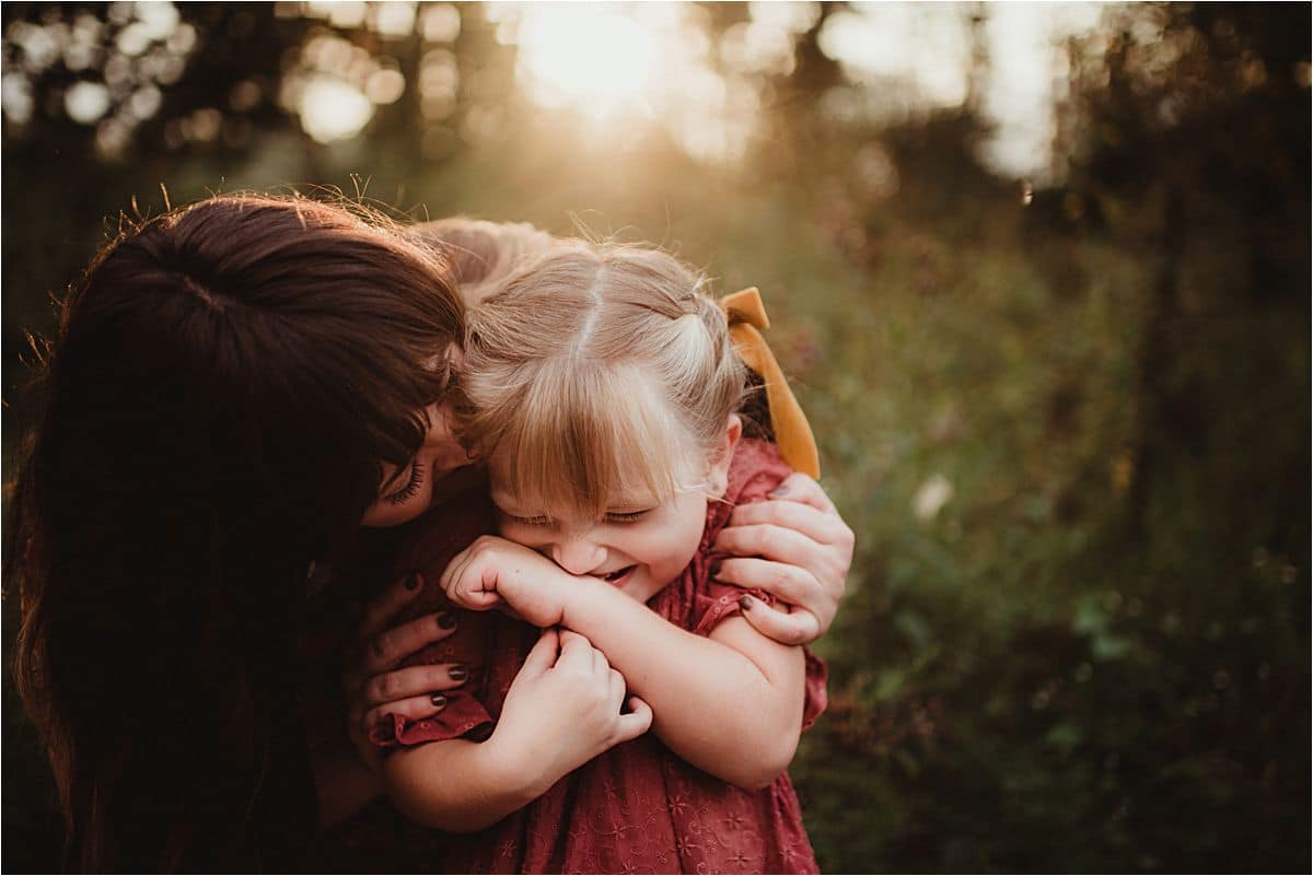 Mama Snuggling Smiling Daughter