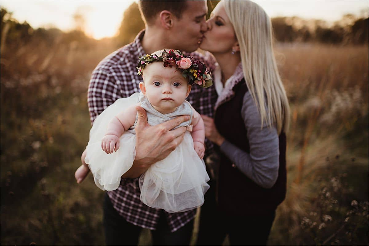 Mom Dad Kissing Holding Baby