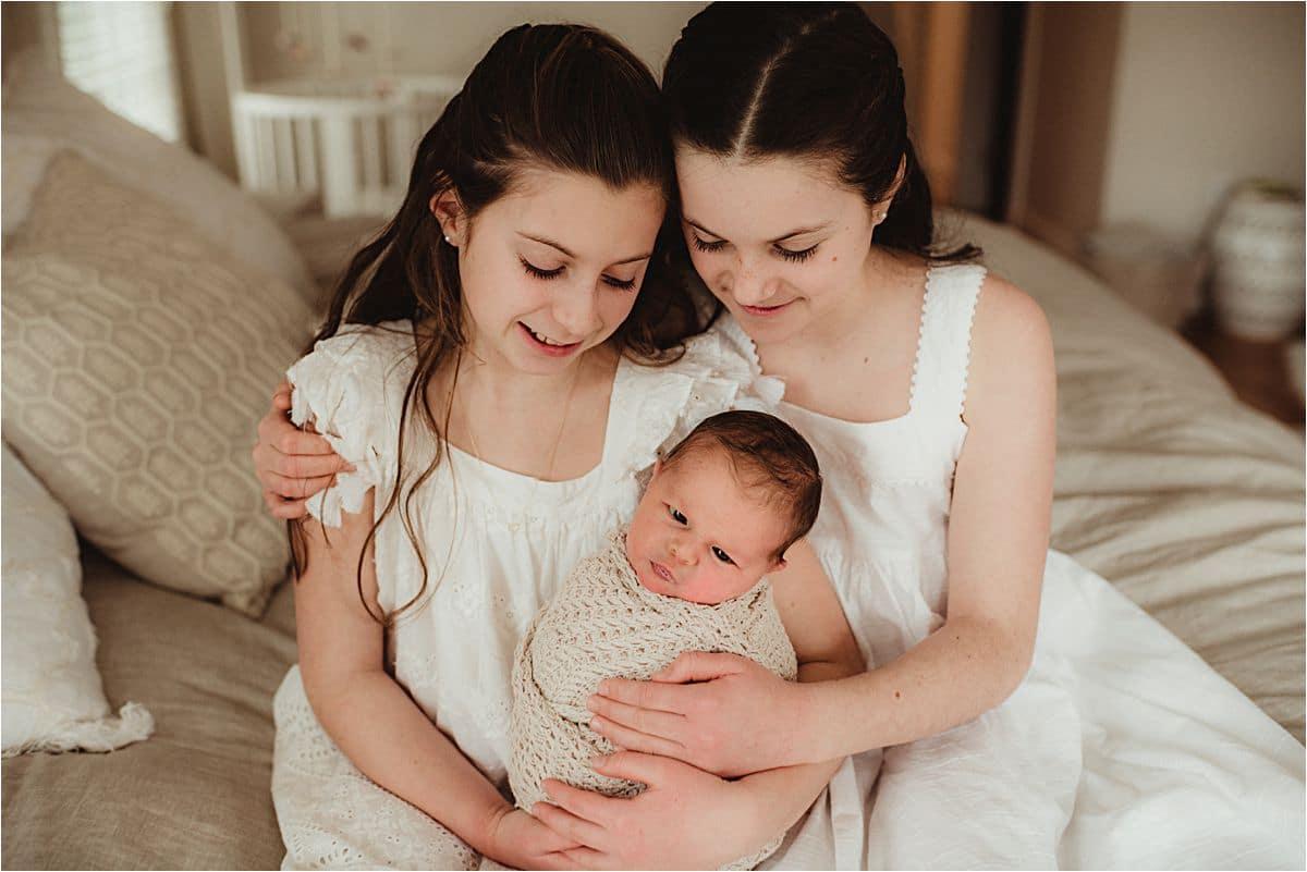 Sisters Holding Newborn
