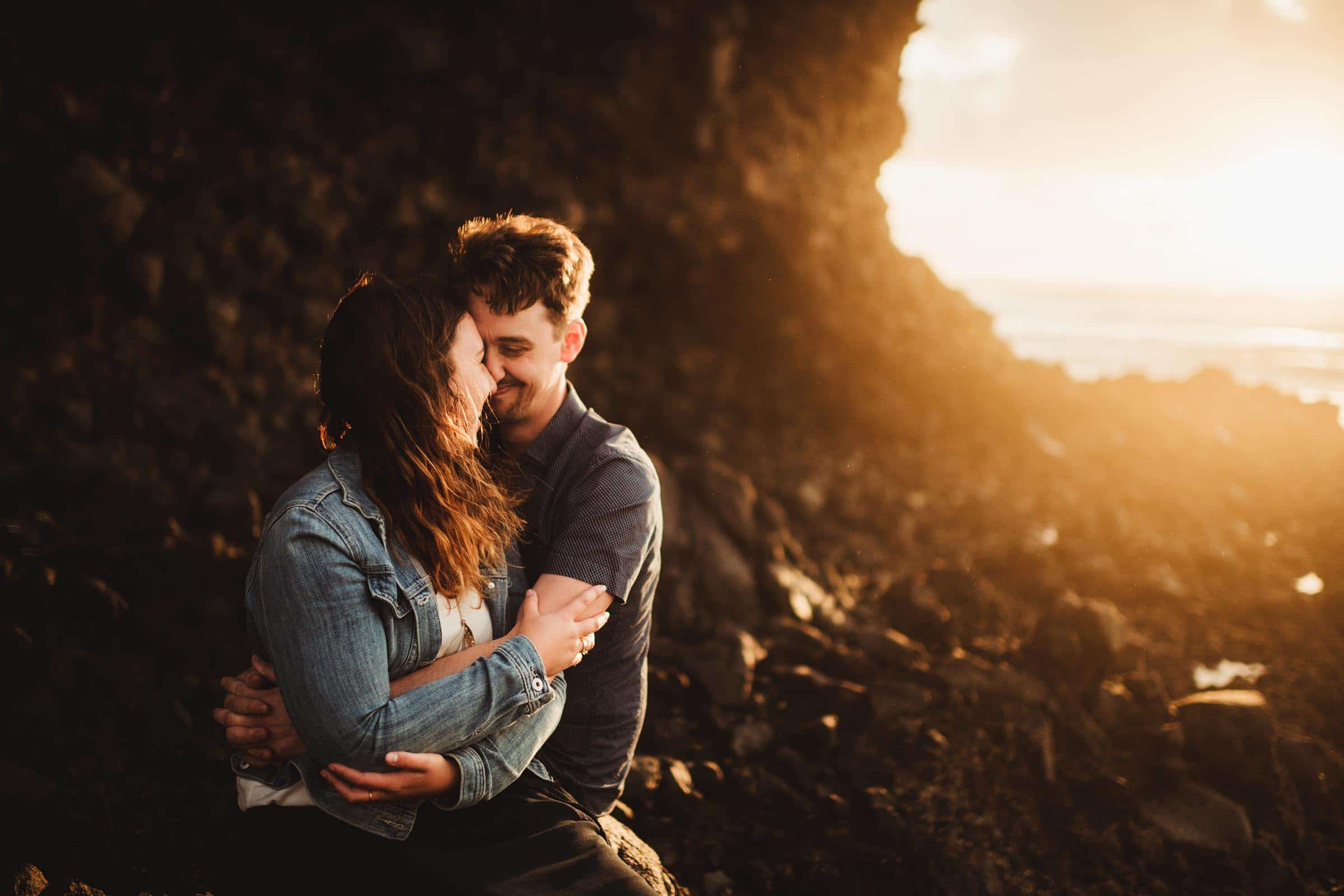 Couple Snugging by Rocks at Sunset