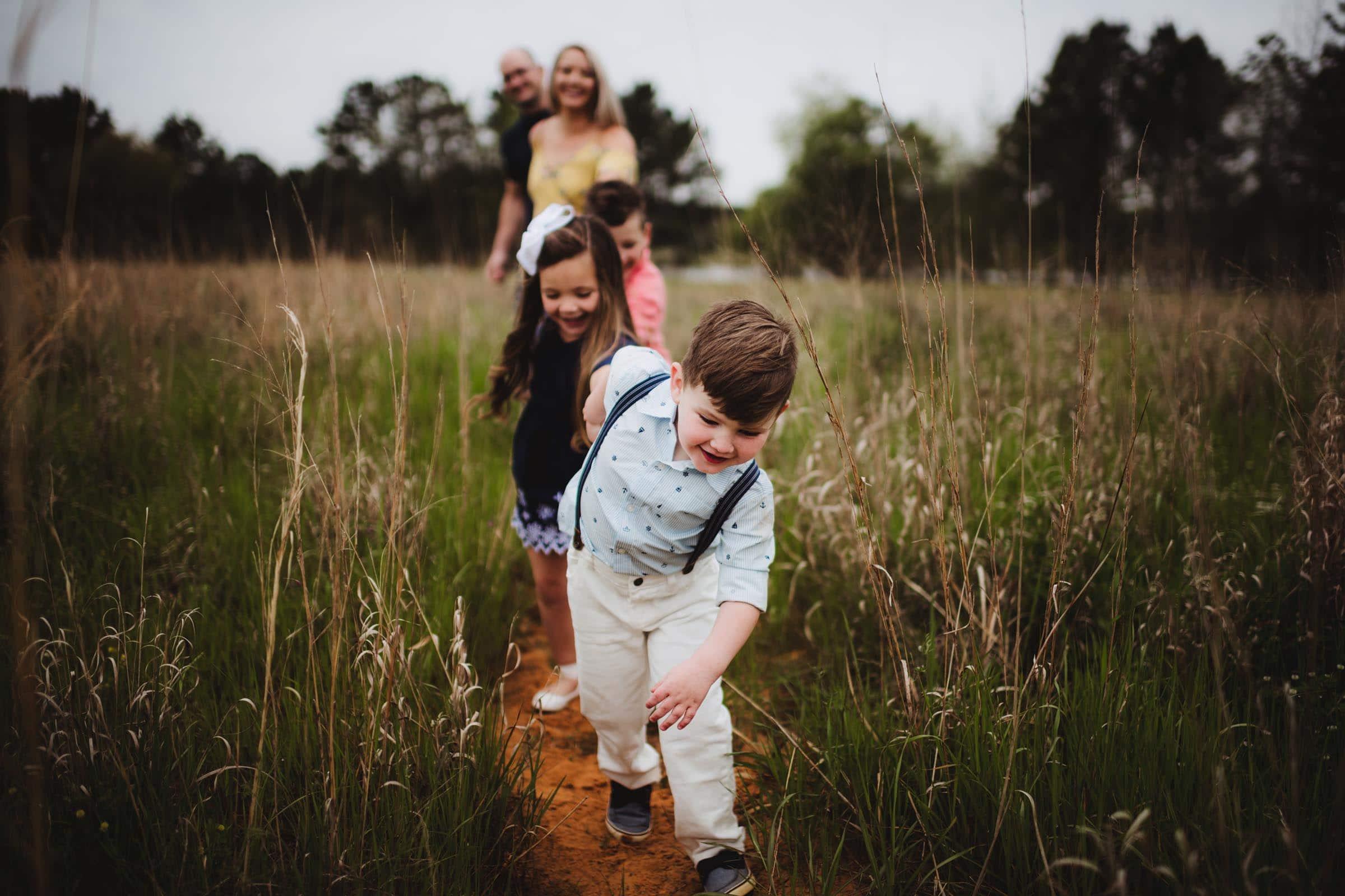 Little Boy Leading Family in Field