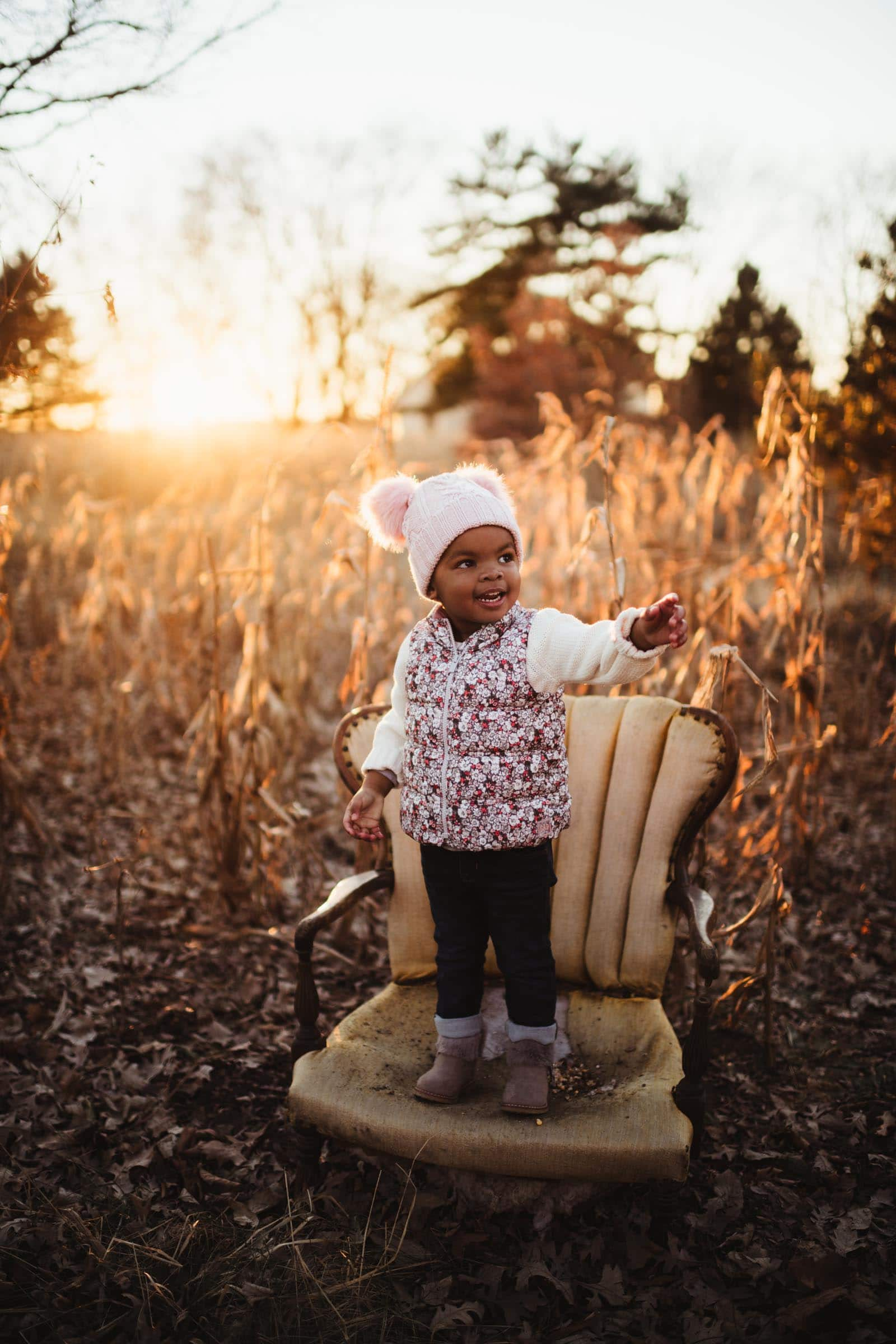Little Girl on Chair in Cornfield at Sunset