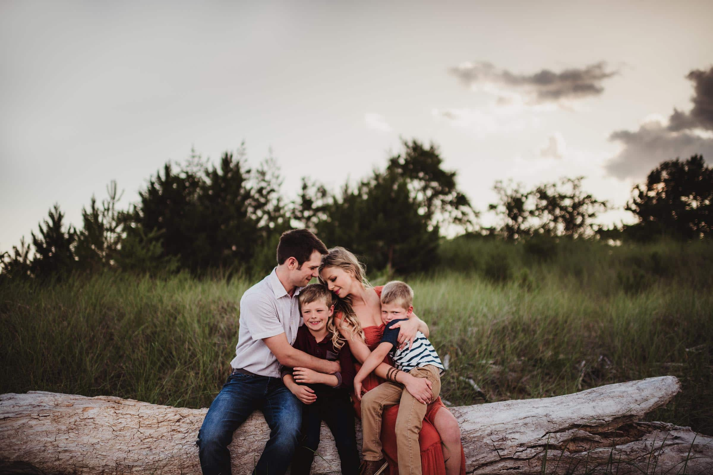 Family Sitting on Log Snuggling
