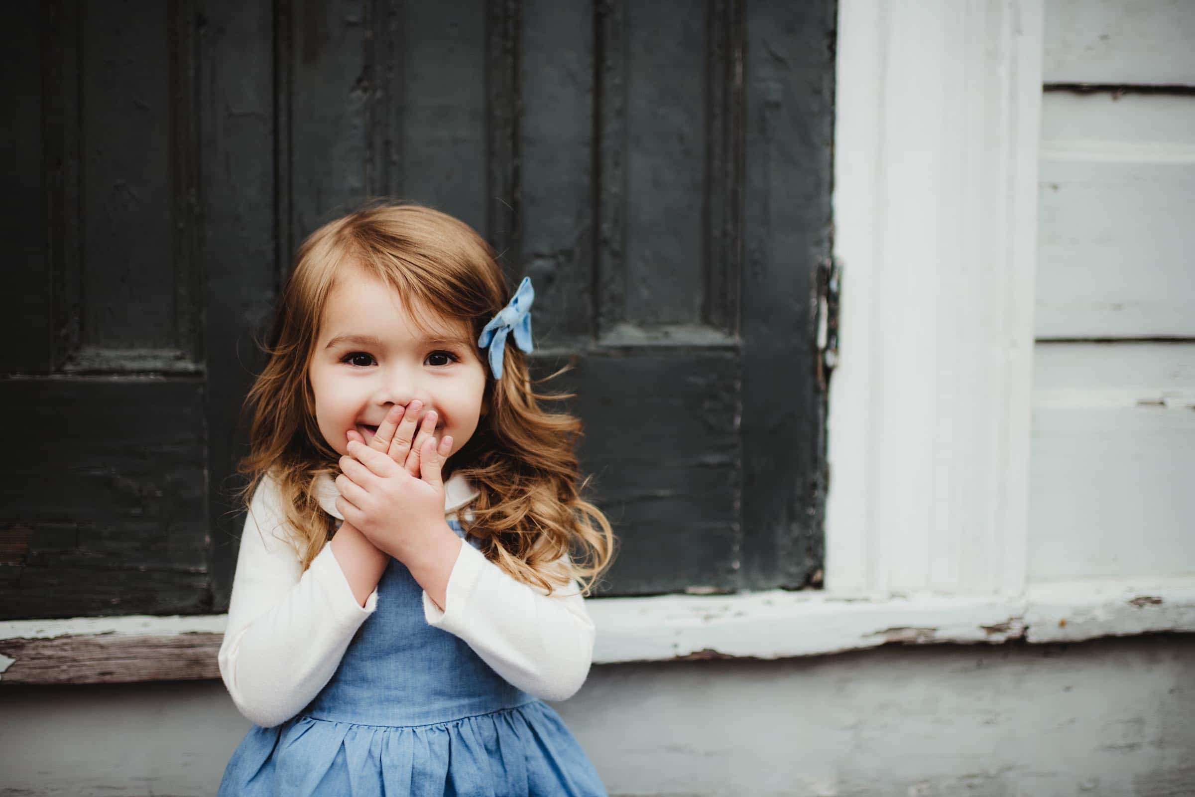 Little Girl Laughing Hands on Mouth